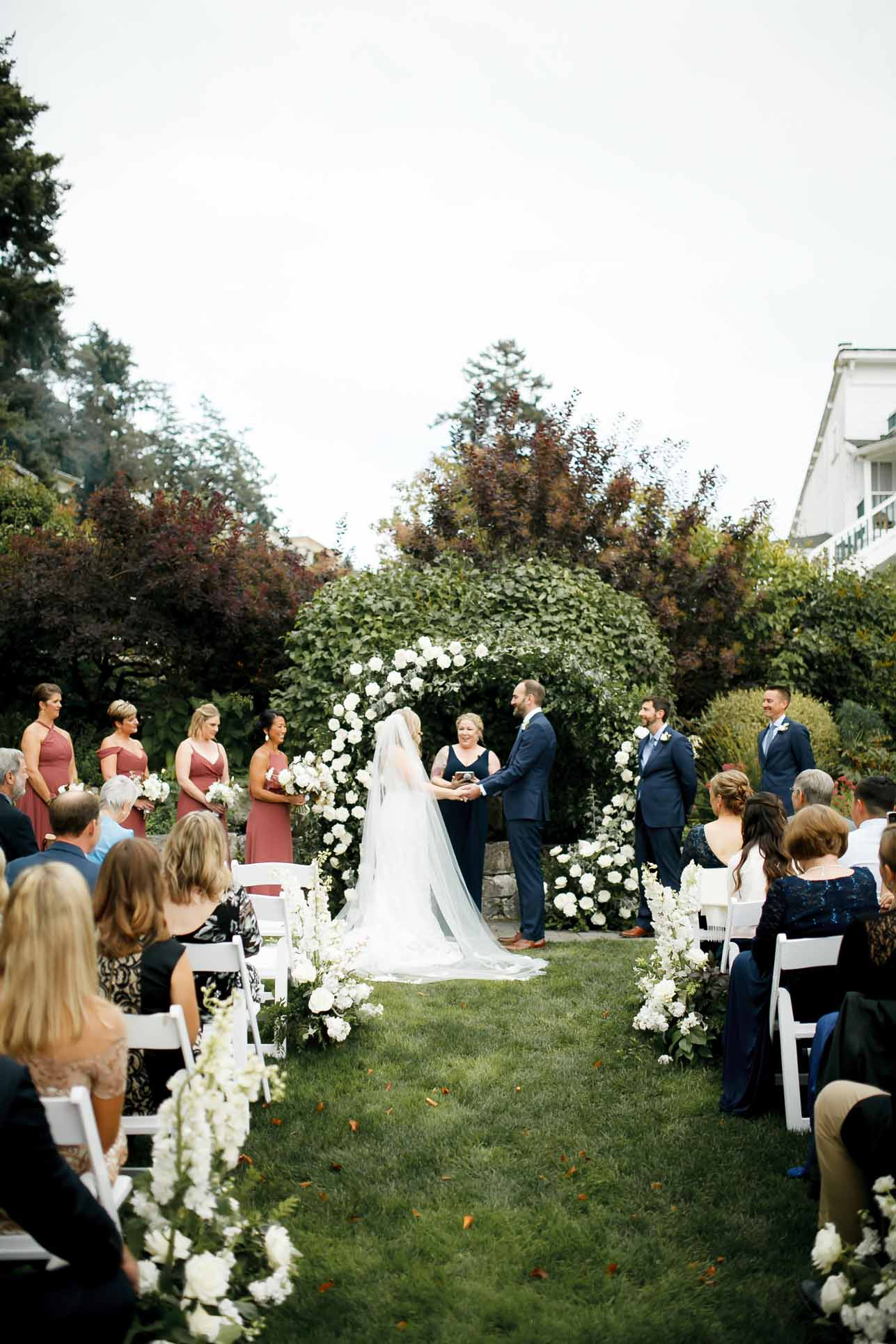 Wedding ceremony in front of white floral arch