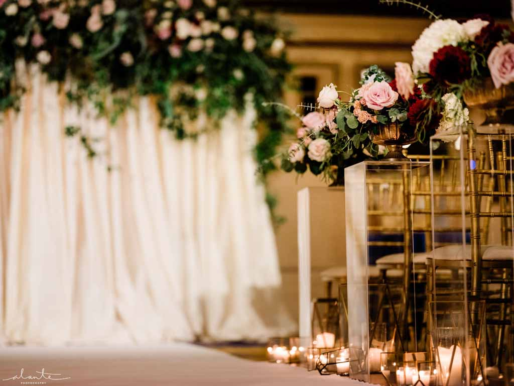Ceremony aisle lined with compote arrangements on top of lucite pedestals and accented by candles