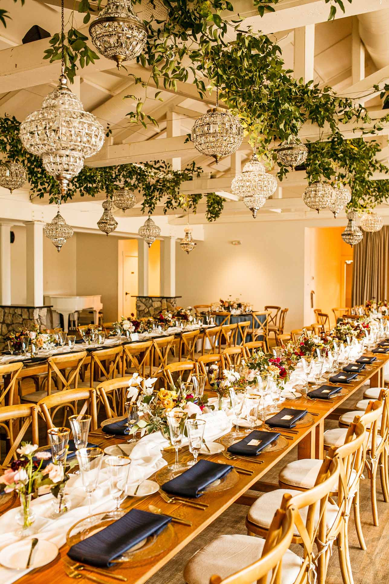Wedding reception with long dinner tables, crustal chandeliers, and Vineyard chairs