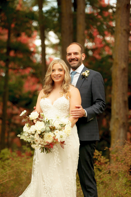 Beautiful wedding couple, bride holding bouquet of fall flowers, designed be Flora Nova Design