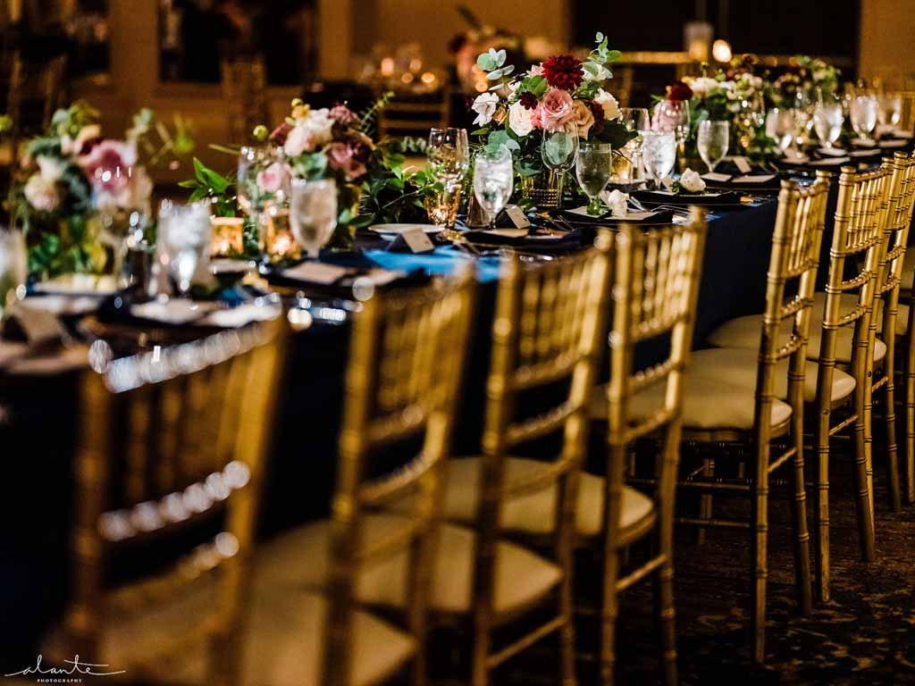 Head table dressed in gold, navy, burgundy, and blush