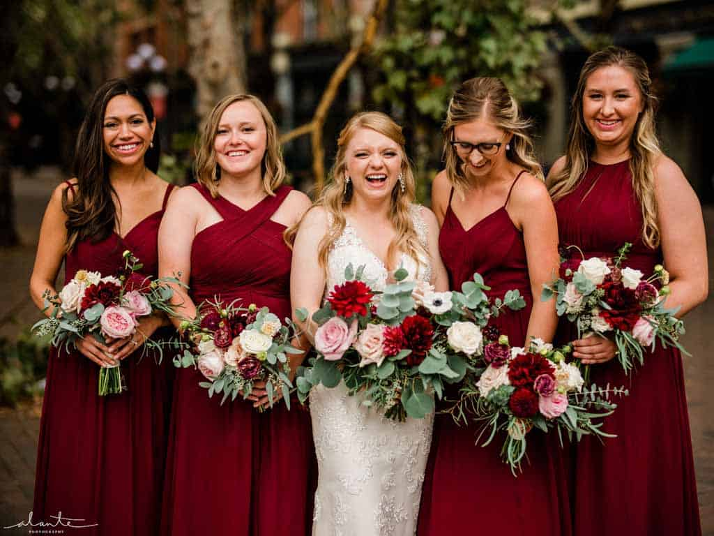 Bride and bridesmaids with burgundy dresses, holding bouquets in burgundy, blush, and cream