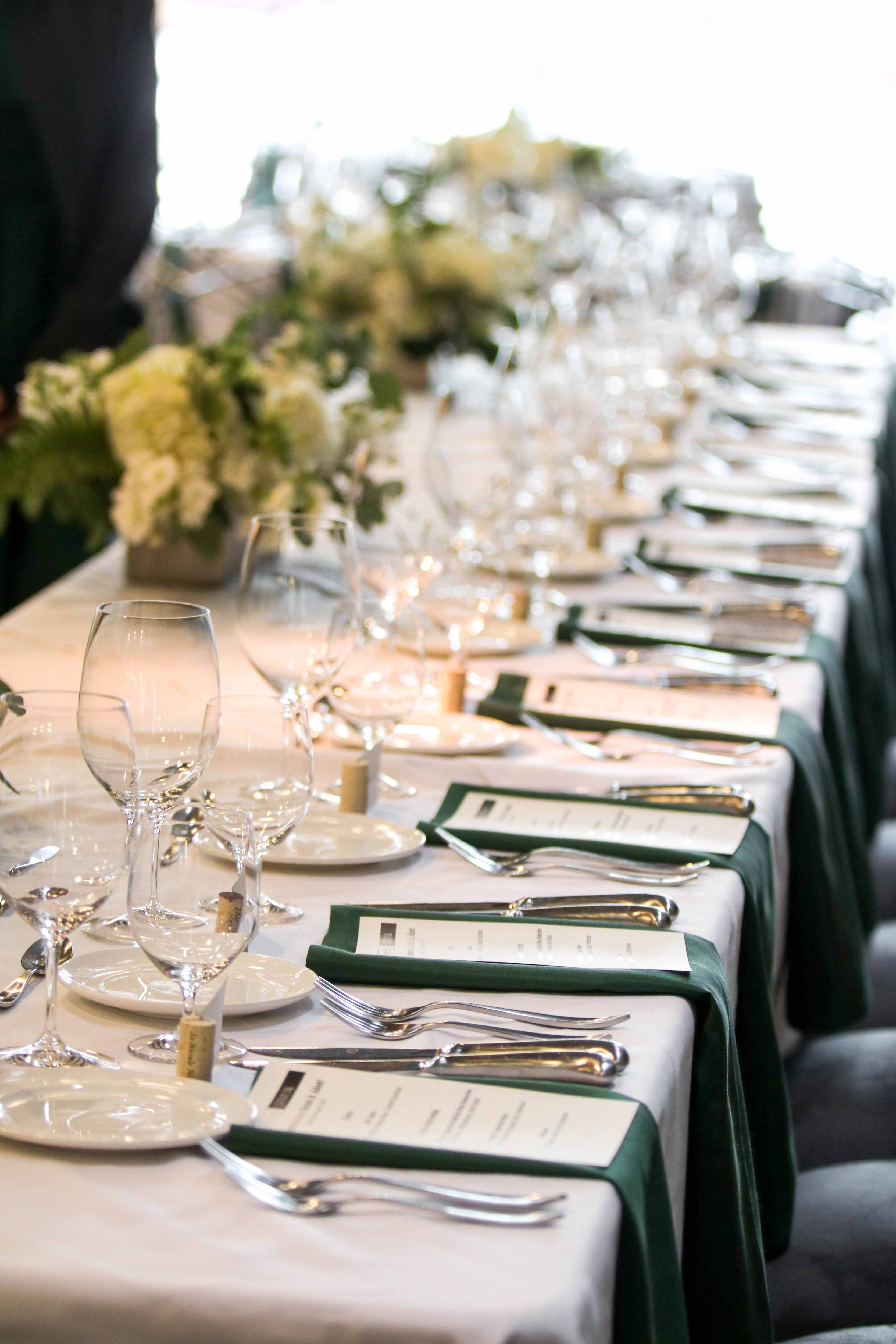long head table with stemware and white flowers