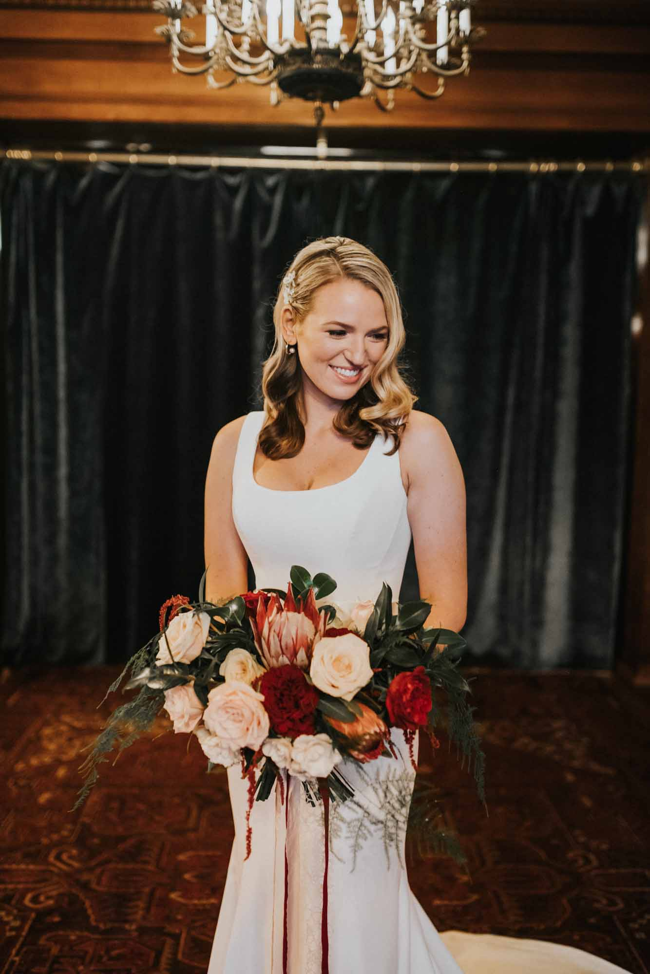 bride holding red, cream, and blush wedding bouquet