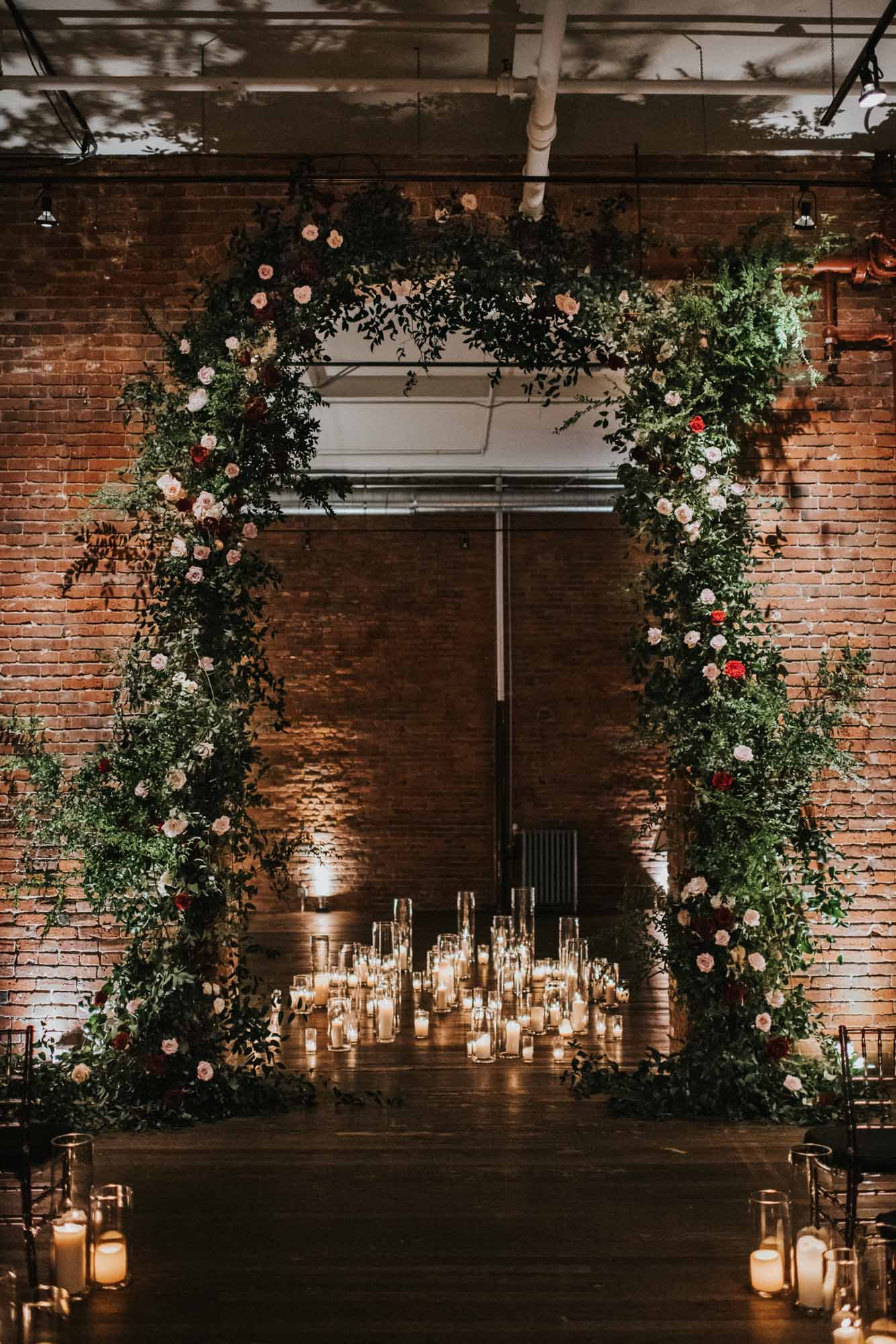 ceremony arch of greenery and roses in brich archway surrounded by candles