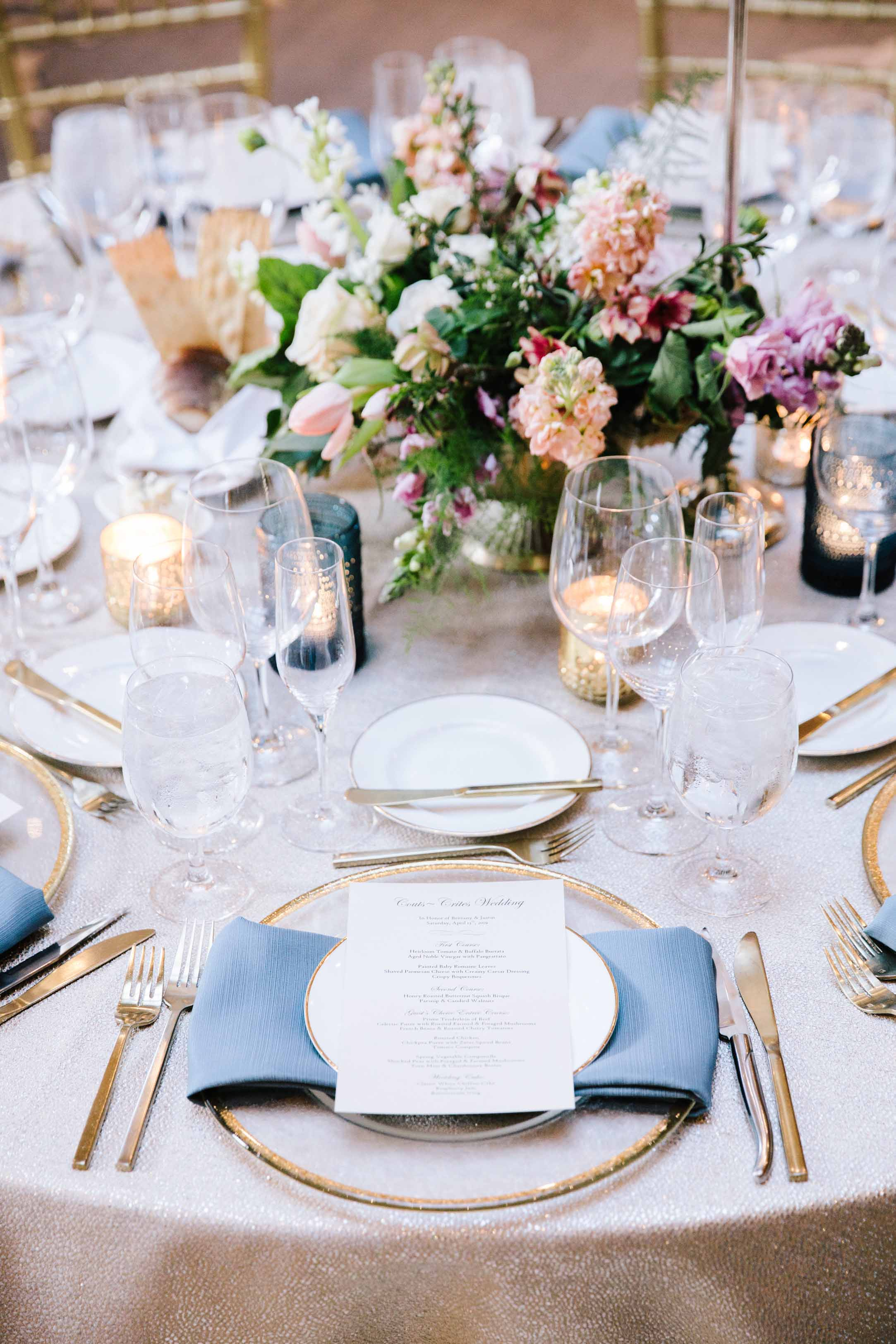 Wedding reception table set with gold flatware and chargers, blue napkins, and a gold compote filled with spring flowers in pink and cream