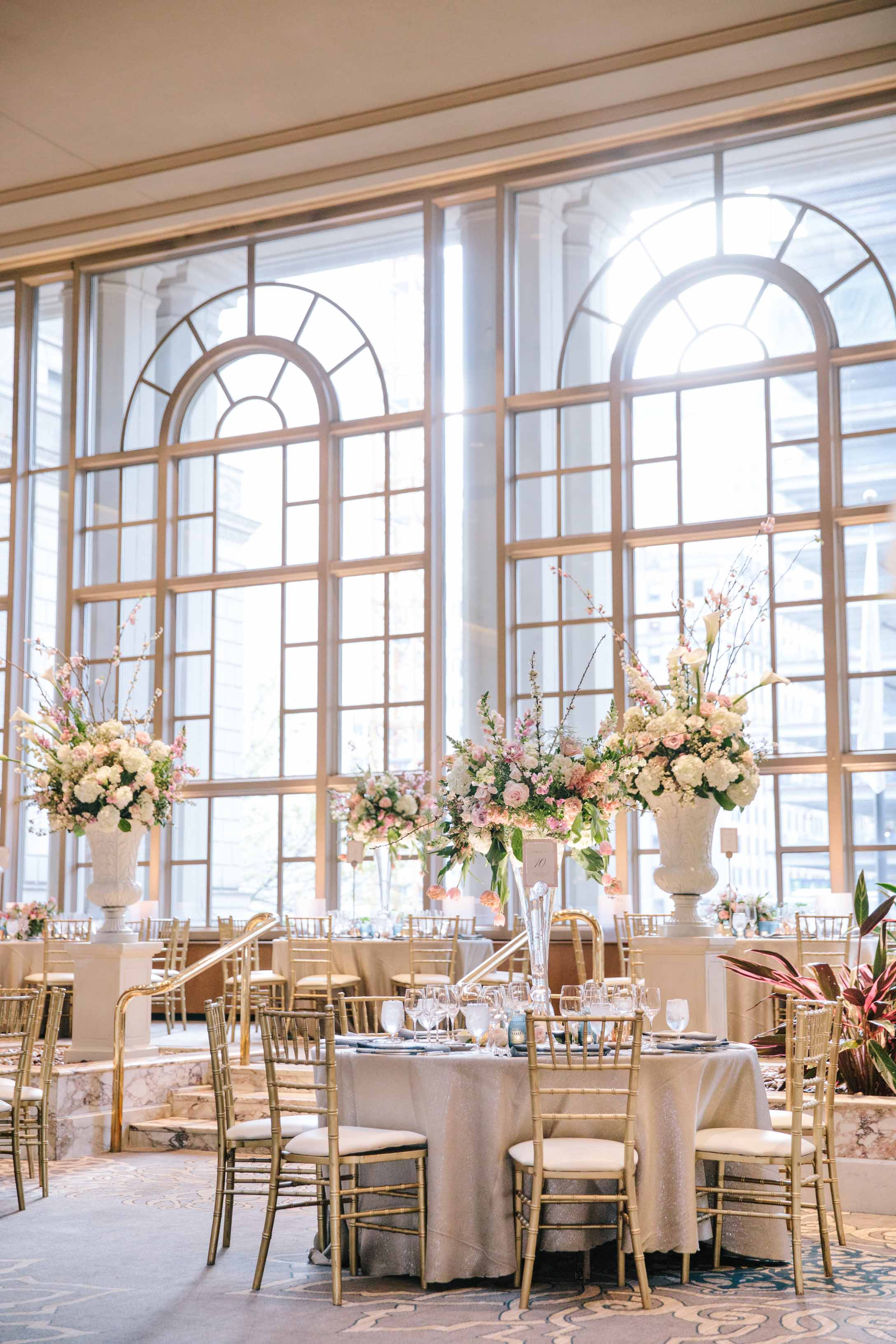 Tall floral arrangements in crystal vases and white urns in the Garden room of the Fairmont Olympic Hotel