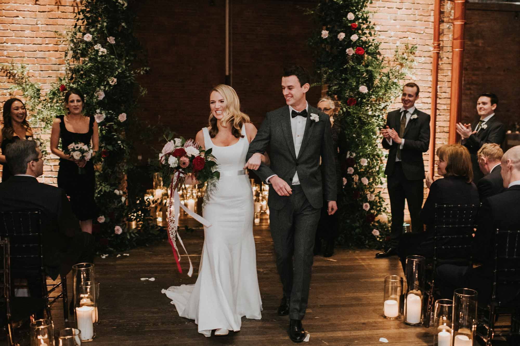 bride and groom face cheering guests after wedding ceremony