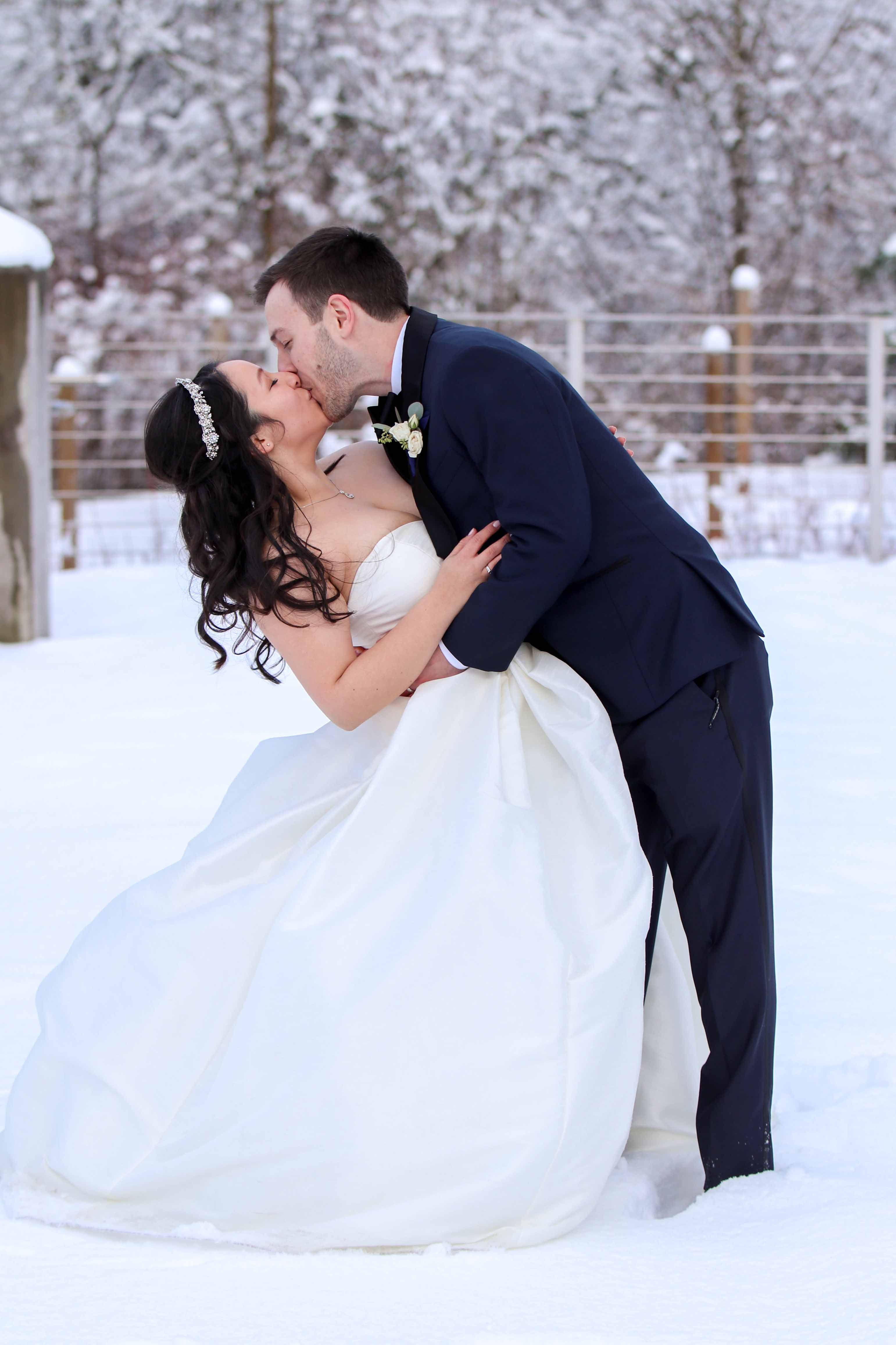 bride and groom share kiss in the snow
