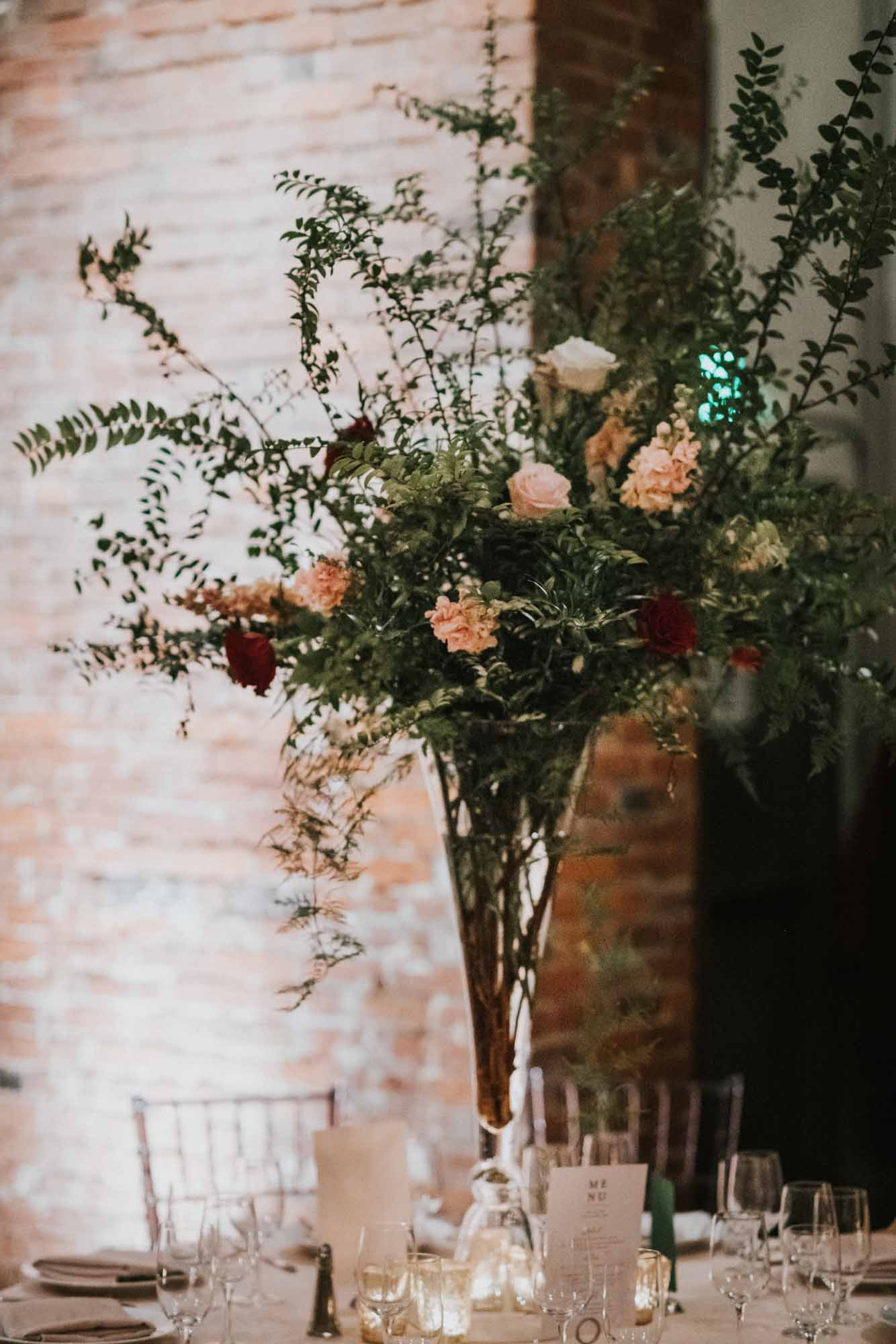 Tall centerpiece with greenery, blush, and burgundy flowers
