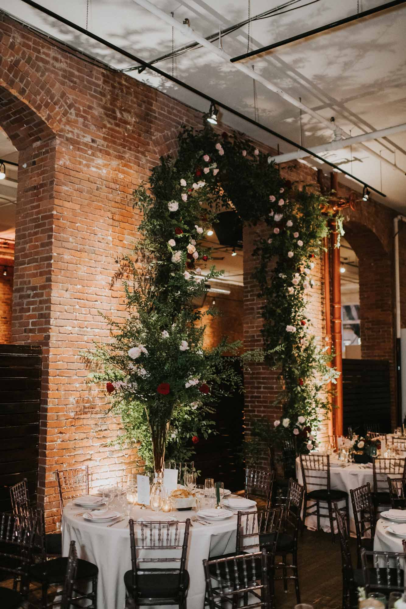 Tall greenery arch attached to brick archway