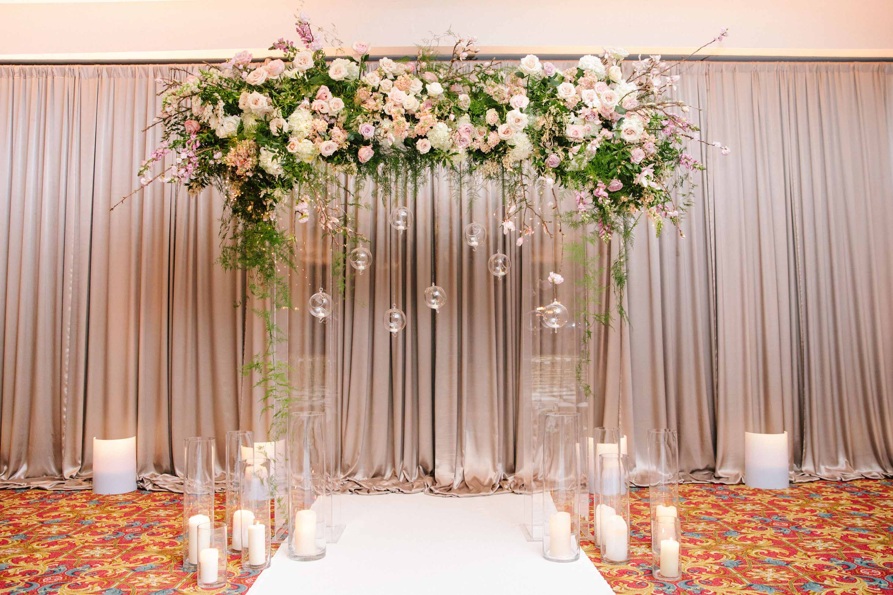 Wedding ceremony arch with flowers, vines, and hanging candles, surrounded by large candles