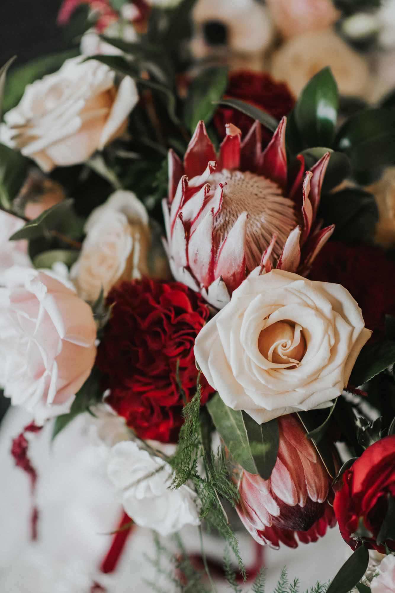 Close up of a cozy winter wedding bouquet with protea and roses