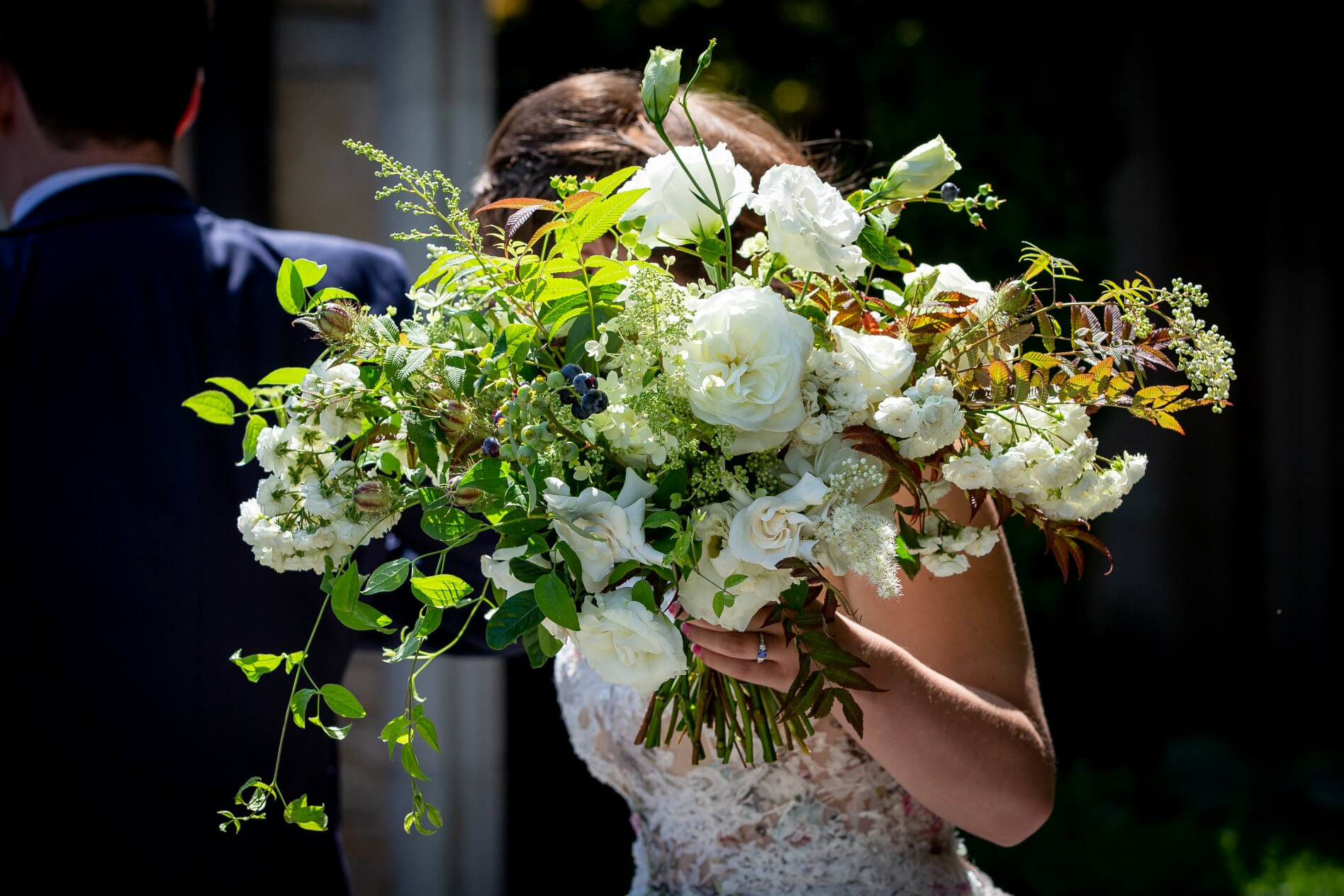 Bride holding midsummer night's wedding bouquet in front of her face