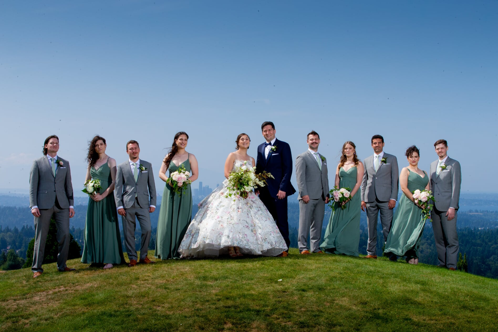 Bride in floral dress and bridemaids in sage bridesmaids dresses standing on grassy hill