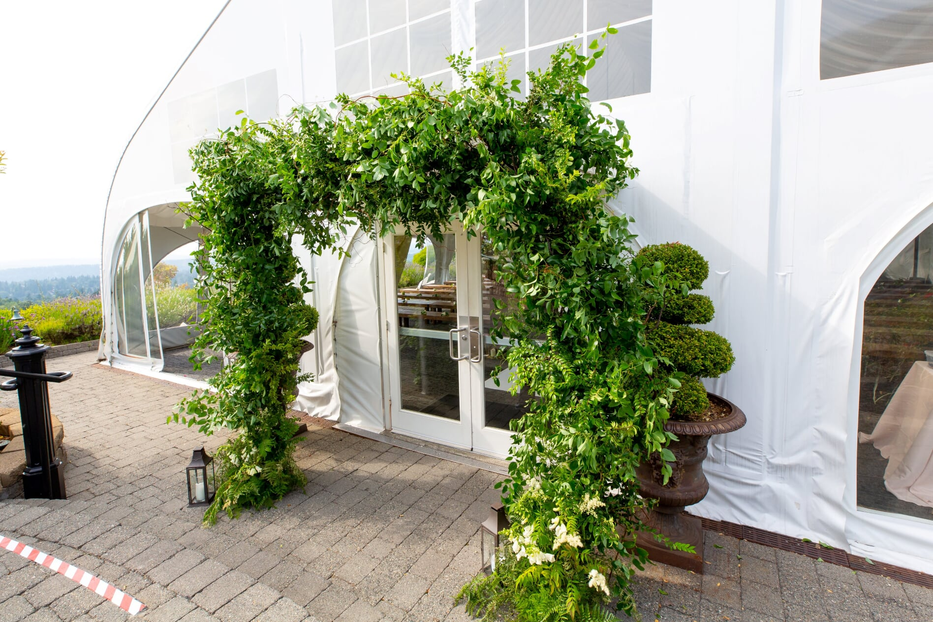 Greenery entrance arch in front of white tent