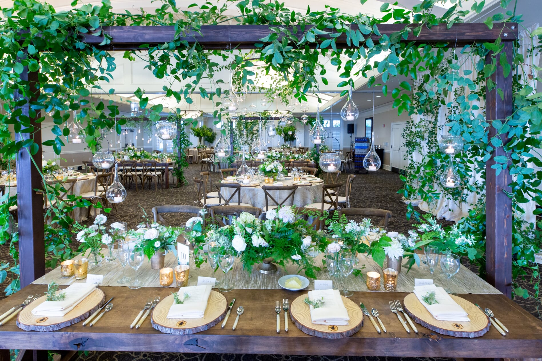 vines hanging over table with hanging votives, over long reception table