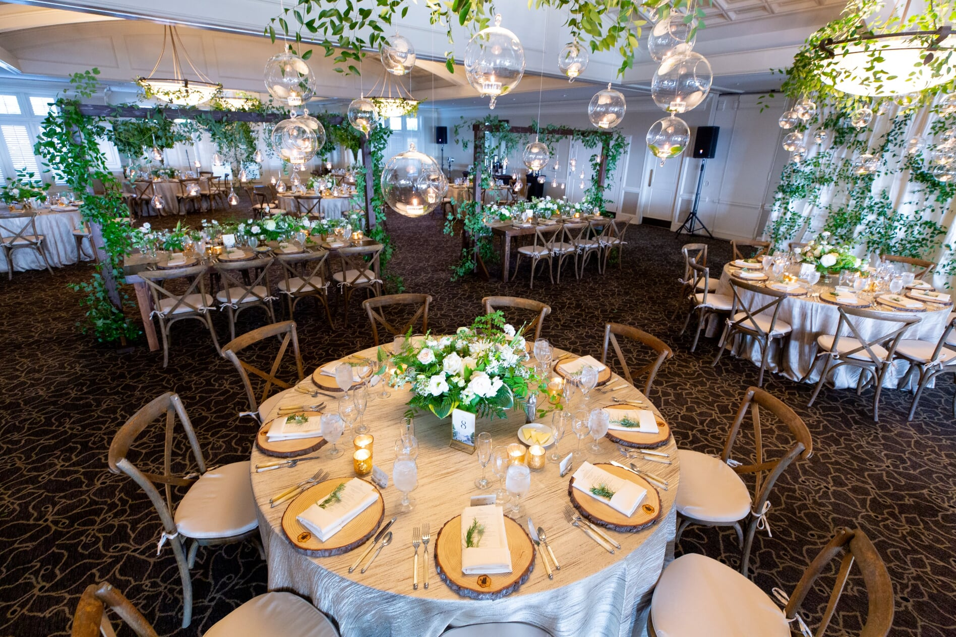 wedding reception with hanging greenery, hanging votives, and wooden chairs