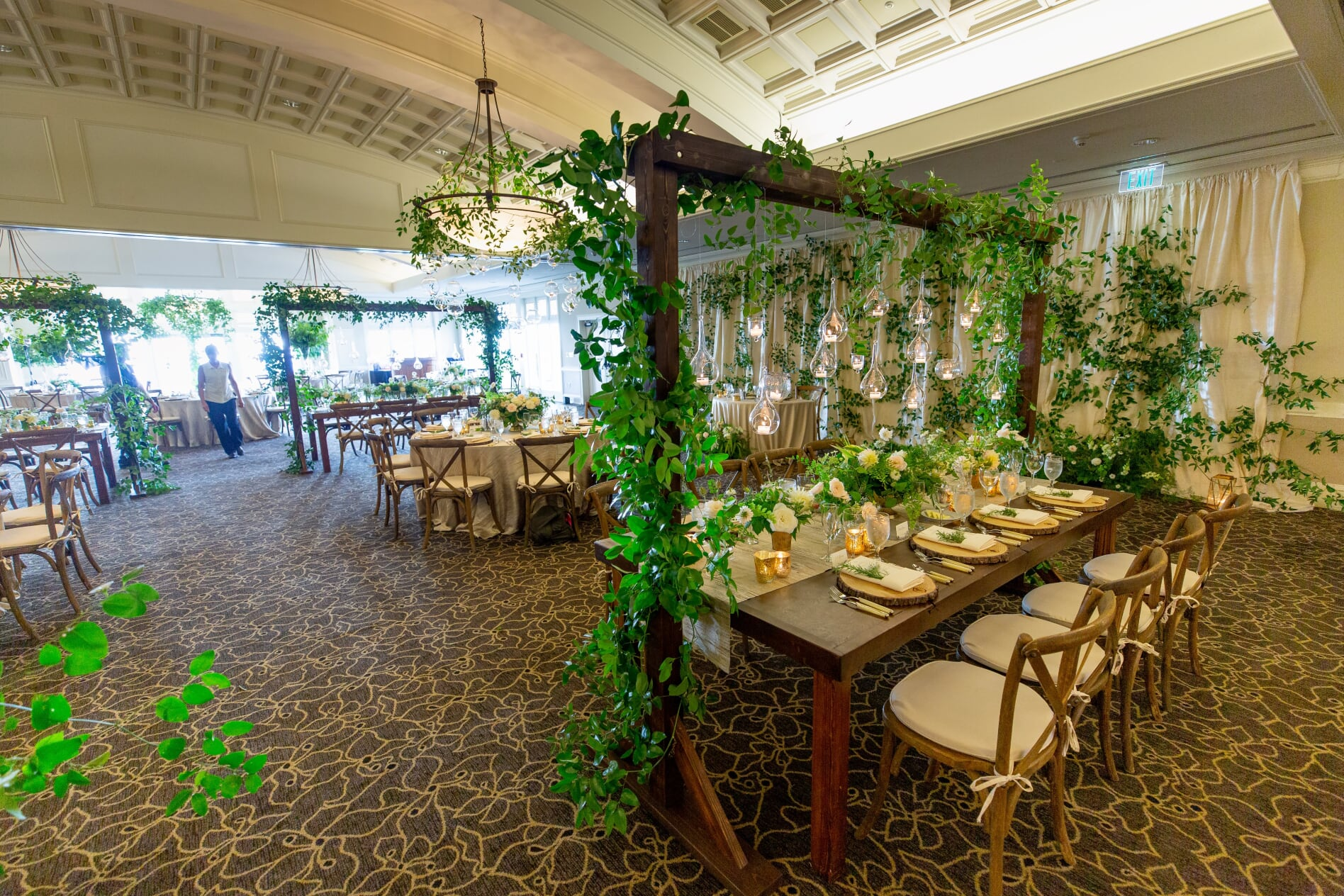Midsummer Night's Dream Wedding Wooden trellis over table hung with vines and hanging candles in ballroom