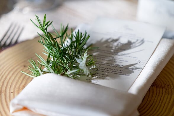 rosemary napkin greens tucked into napkin with menu card at wedding reception