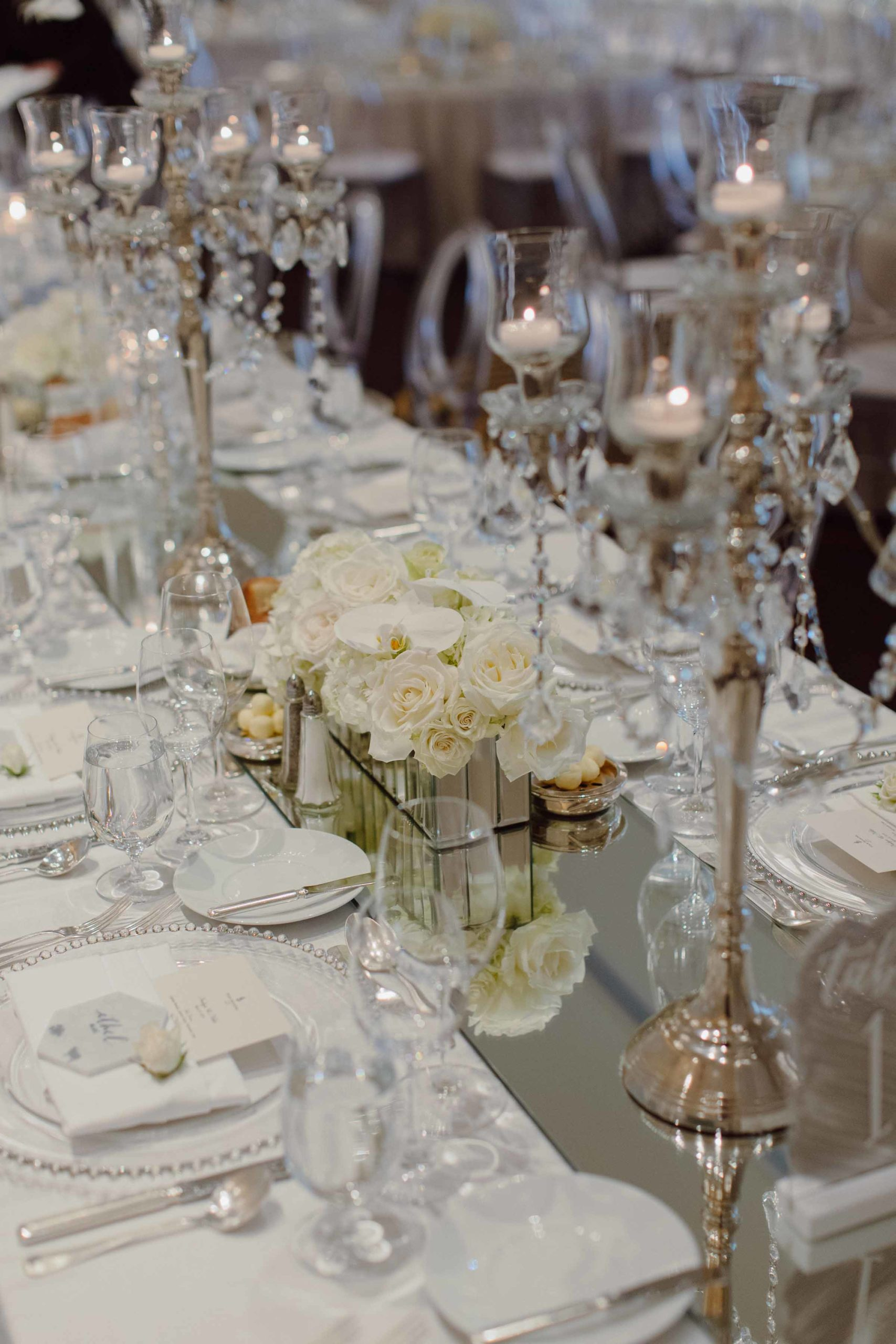 long wedding reception table with mirrored runner, crystal candelabras, and all white roses