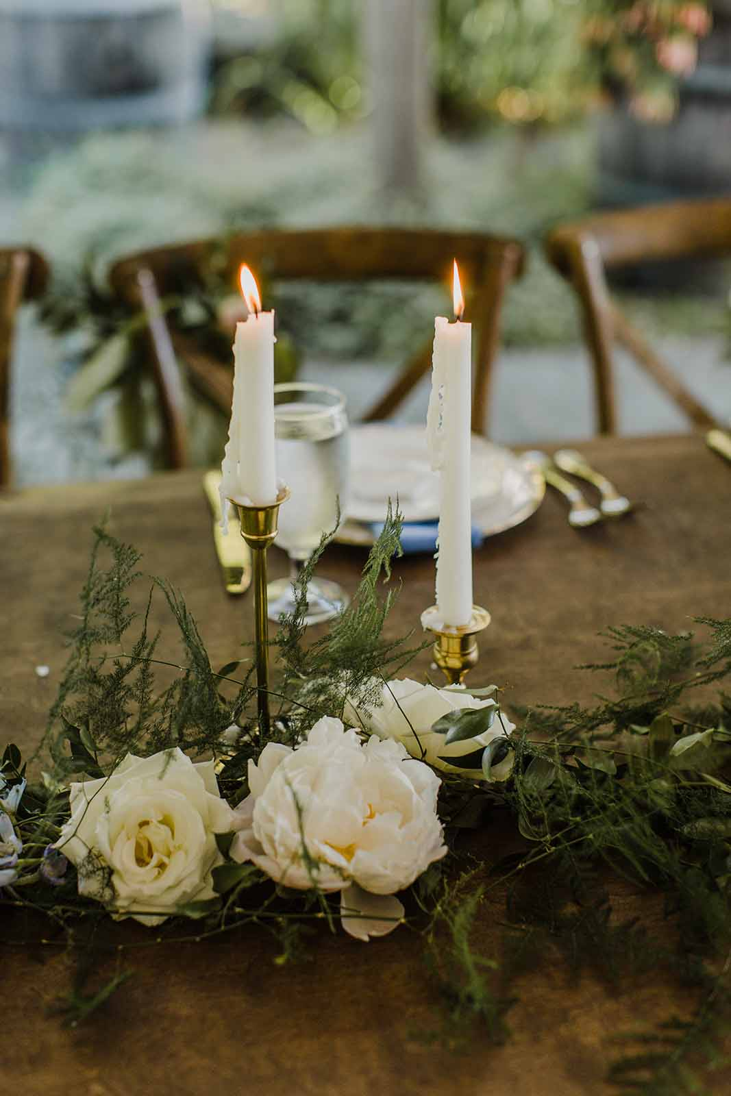 Head Table decor featuring taper candles, greenery garland, and cream roses.