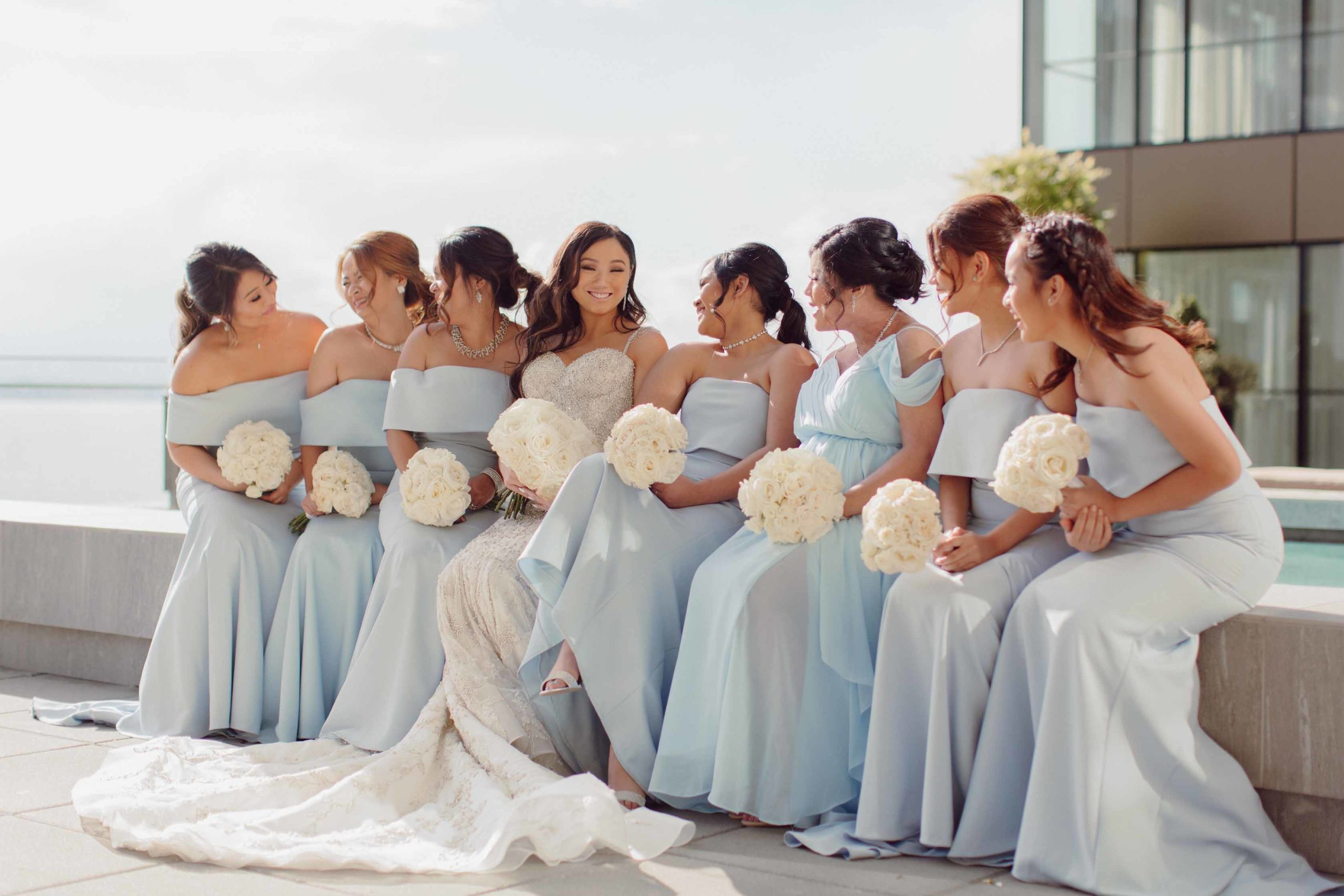 bridesmaids in blue dresses with all white rose bouquets