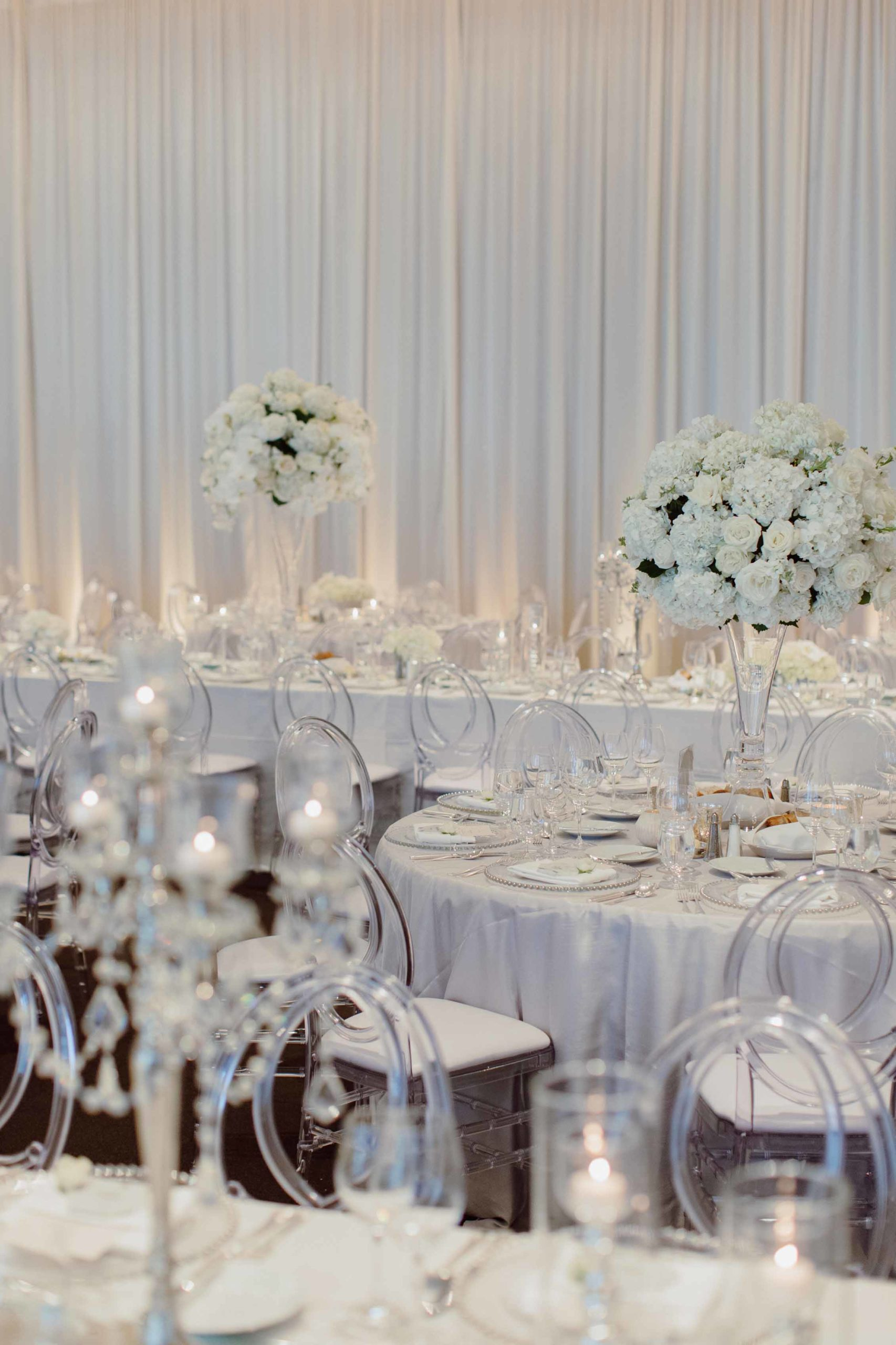 all white wedding reception at the Four Seasons Seattle with draped ballroom and tall centrerpieces with phalenopsis orchids