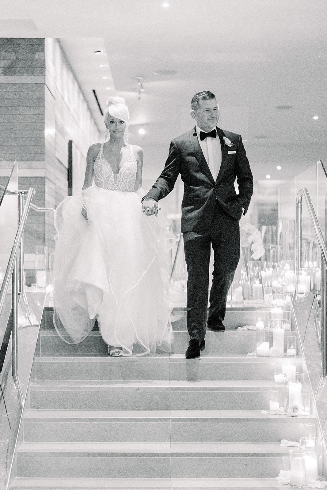 Bride and groom descend the candle lined staircase at Four Seasons Seattle for their white orchid wedding | Flora Nova Design