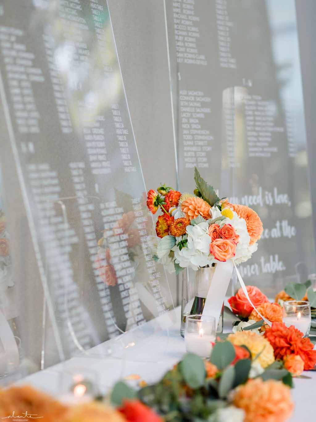Seating chart with orange and grey flowers for a orange summer wedding at Chihuly