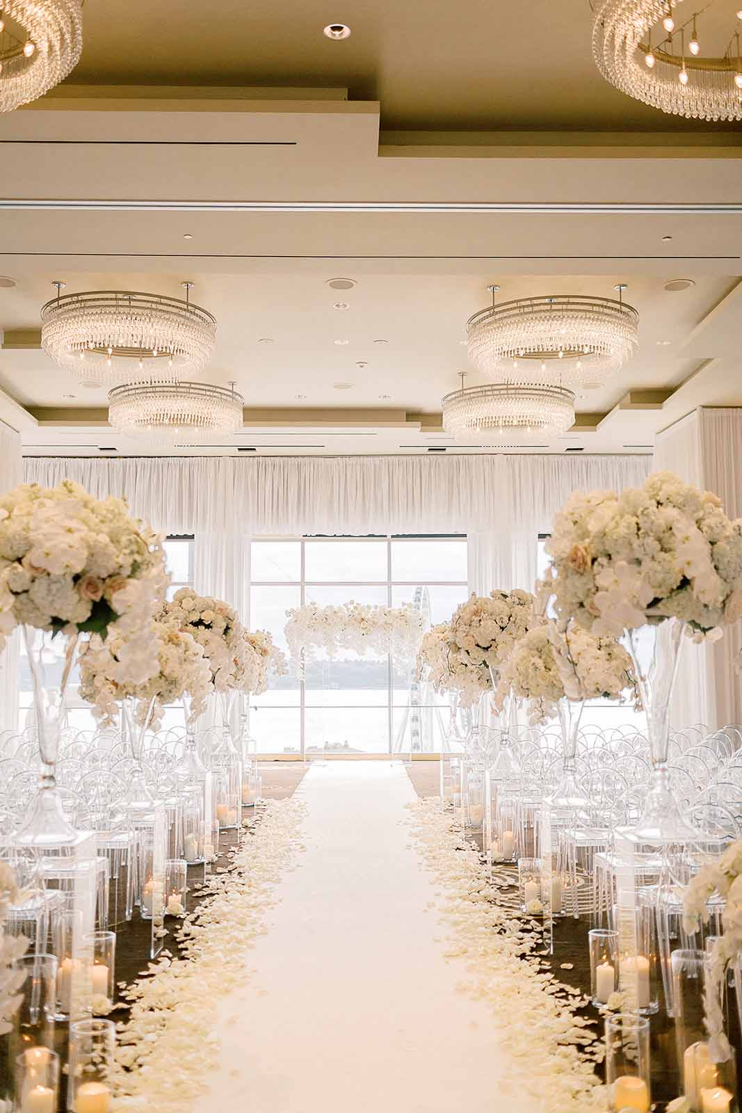 Formal white orchid filled wedding ceremony at Four Seasons Seattle ballroom aisle lined with tall white floral arrangements designed by Flora Nova Design