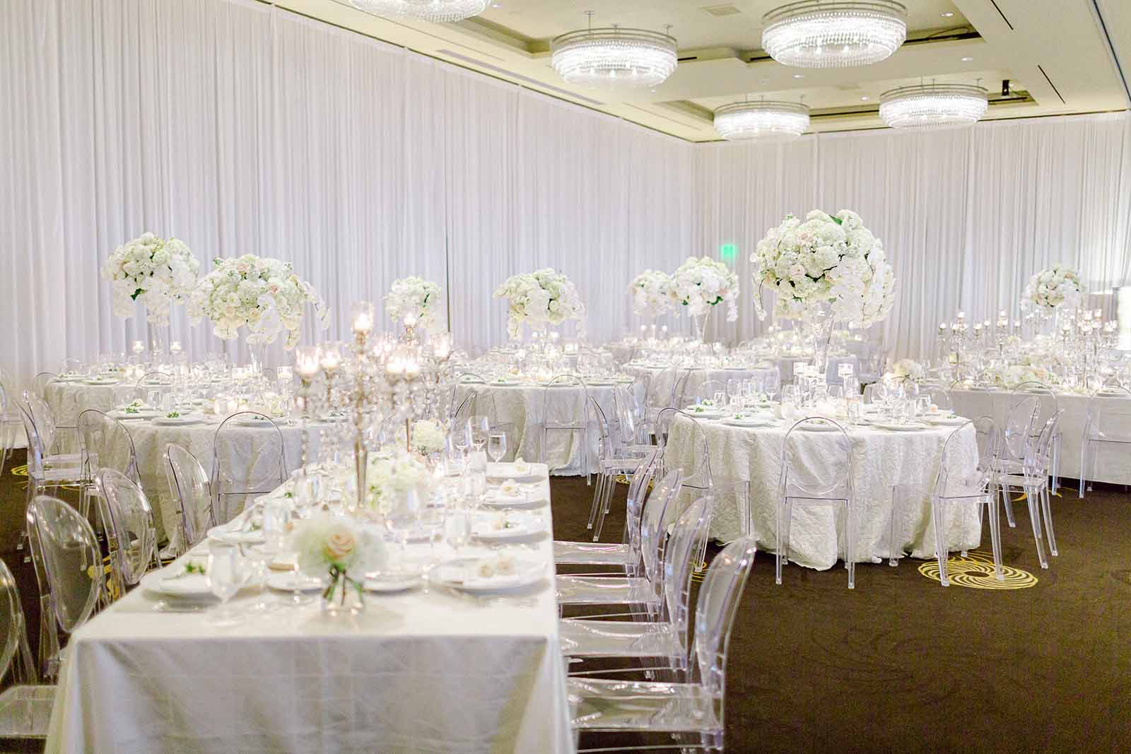 Formal white orchid wedding in the draped ballroom at Four Seasons Seattle with a mix of round and rectangle tables and lucite ghost chairs | Flora Nova Design