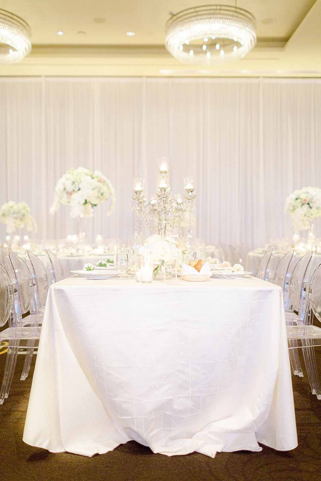 Long table with white table cloth and low white floral and candelabras in a white draped ballroom