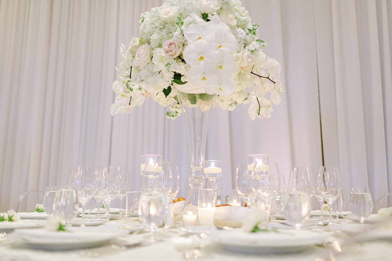 Tall white floral centerpiece with white orchids and stemmed hurricane candles surrounding it designed by Flora Nova Design Seattle