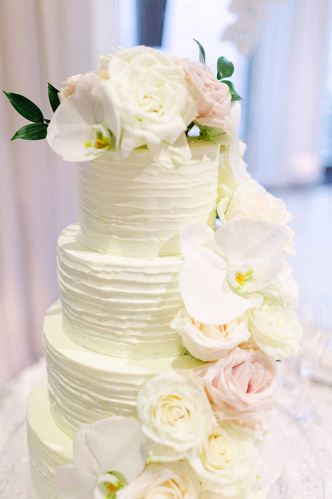 White tiered wedding cake with a waterfall of fresh orchids and roses cascading down it