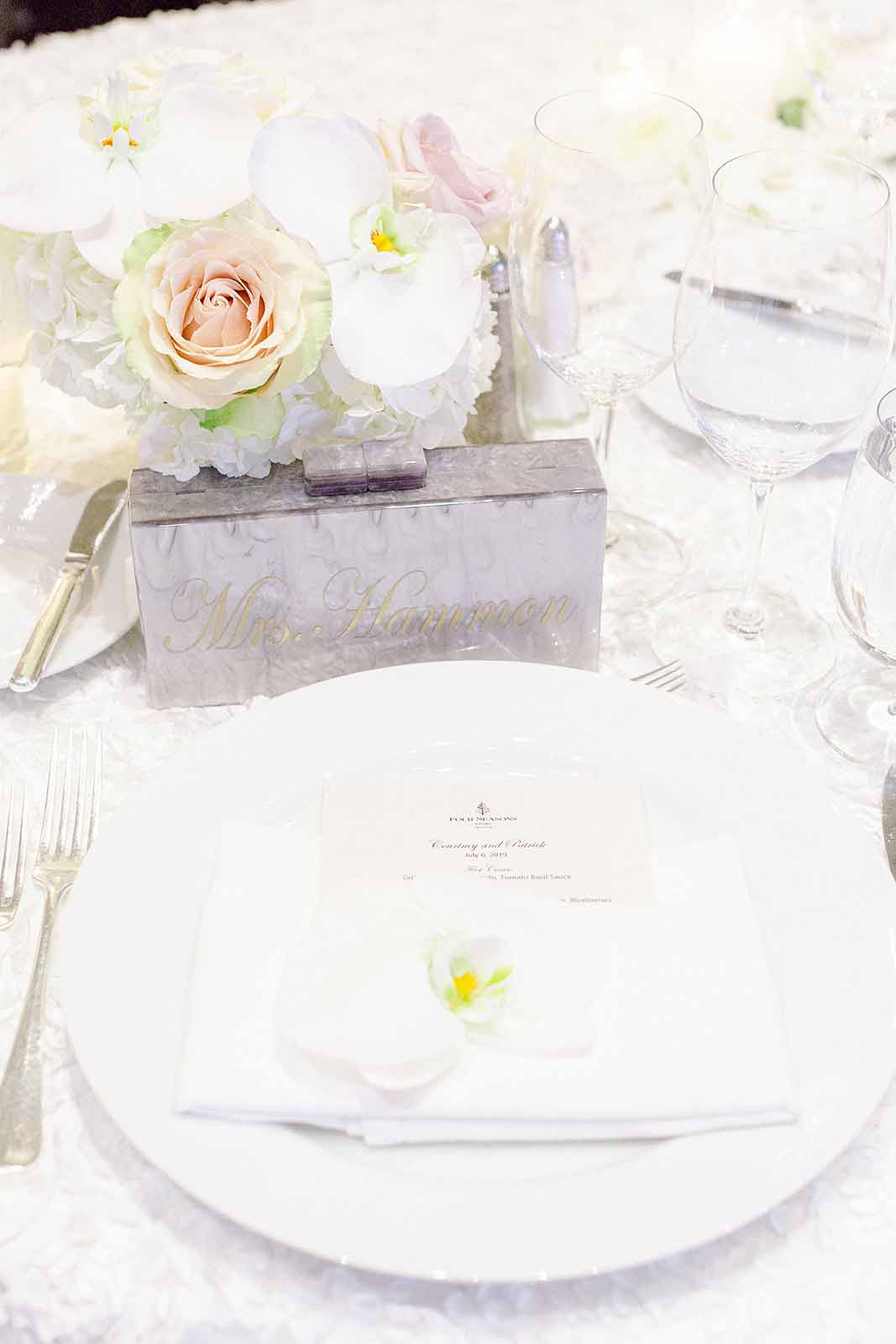 Place setting with white charger plate and white orchid napkin flower with a low white floral centerpiece designed by Flora Nova Design Seattle