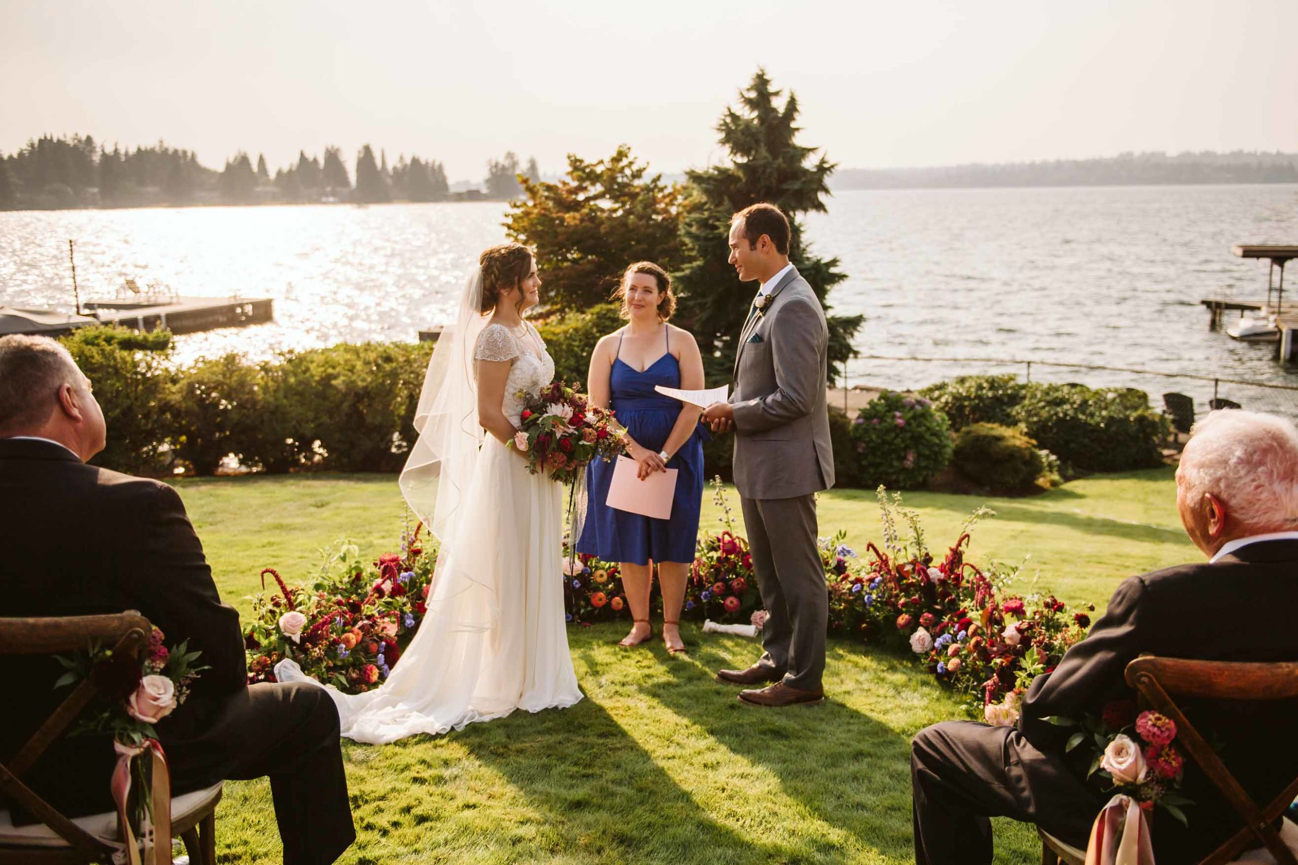 Grounded floral arch of lush burgundy and blush summer flowers with pops of blue for a summer outdoor Lake Washington Wedding | Flora Nova Design Seattle