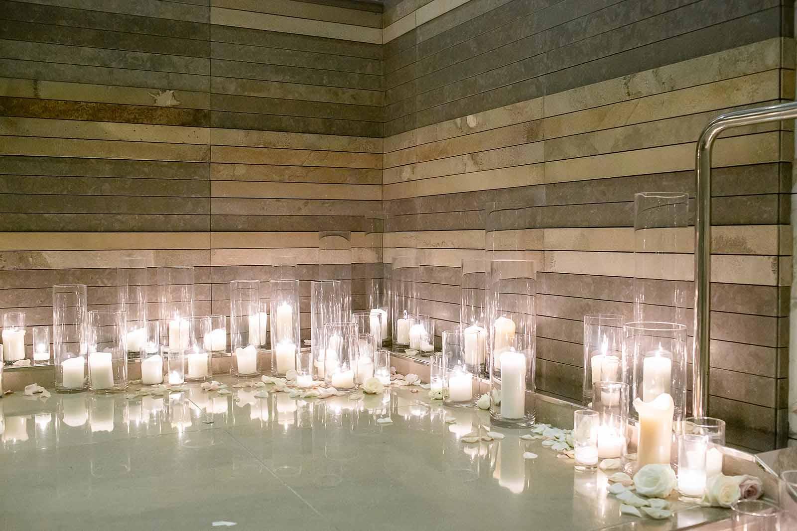 White hurricane candles line the staircase leading to a summer ballroom wedding at Four Season Seattle | Flora Nova Design