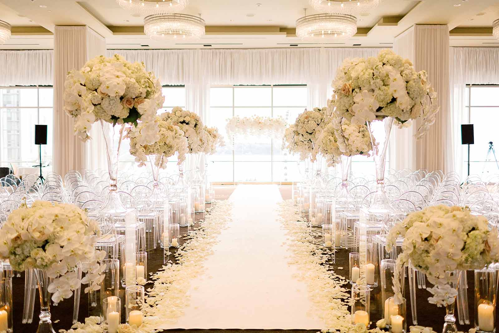 Formal white orchid wedding ballroom ceremony setup with white aisle runner lined with rose petals, candles, and tall floral arrangements on lucite pillars designed by Flora Nova Design