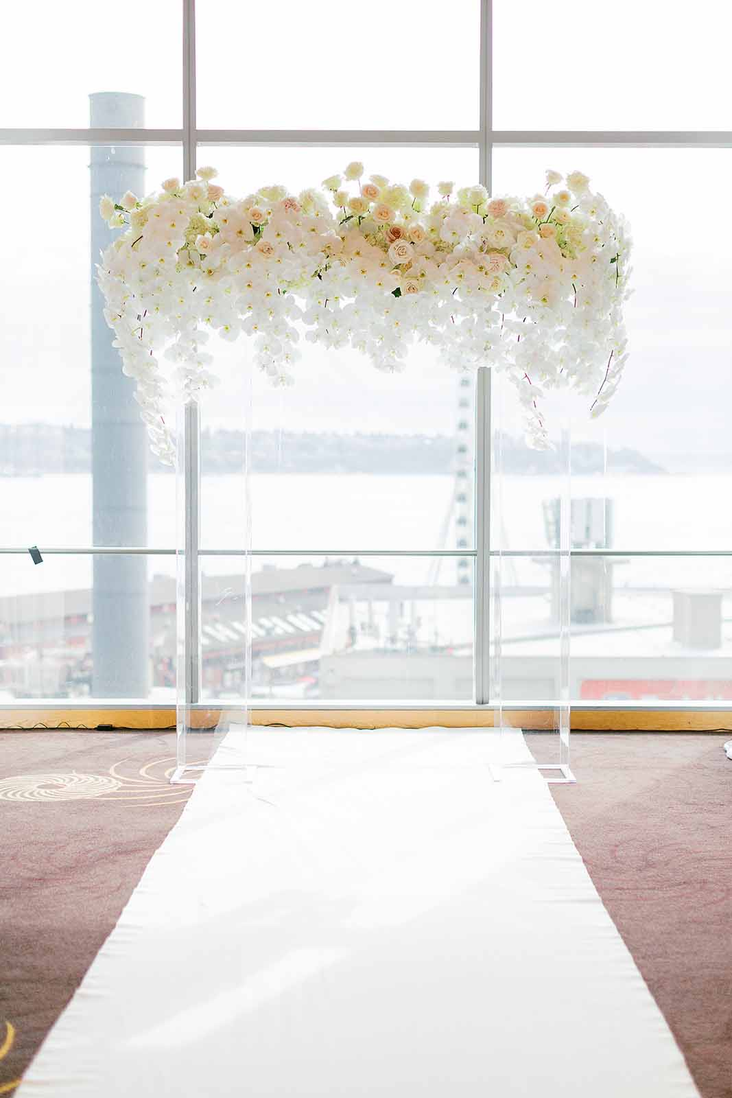White floral and lucite wedding arch covered in orchids and roses at a formal wedding in Seattle