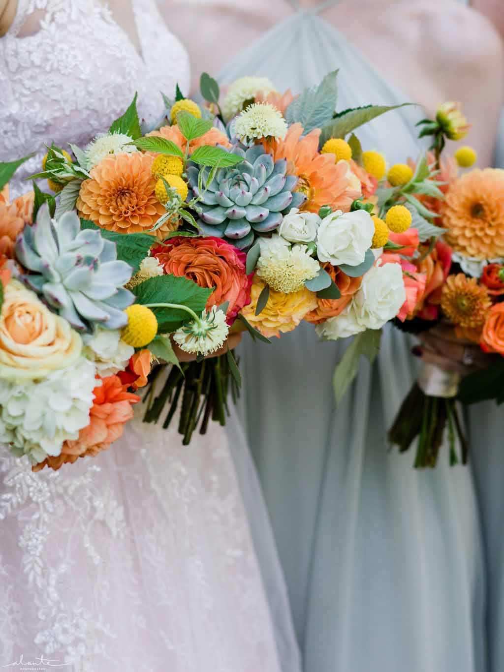 Summer bridal bouquet in orange, yellow, and grey colors with succulents, roses, and craspedia flowers.