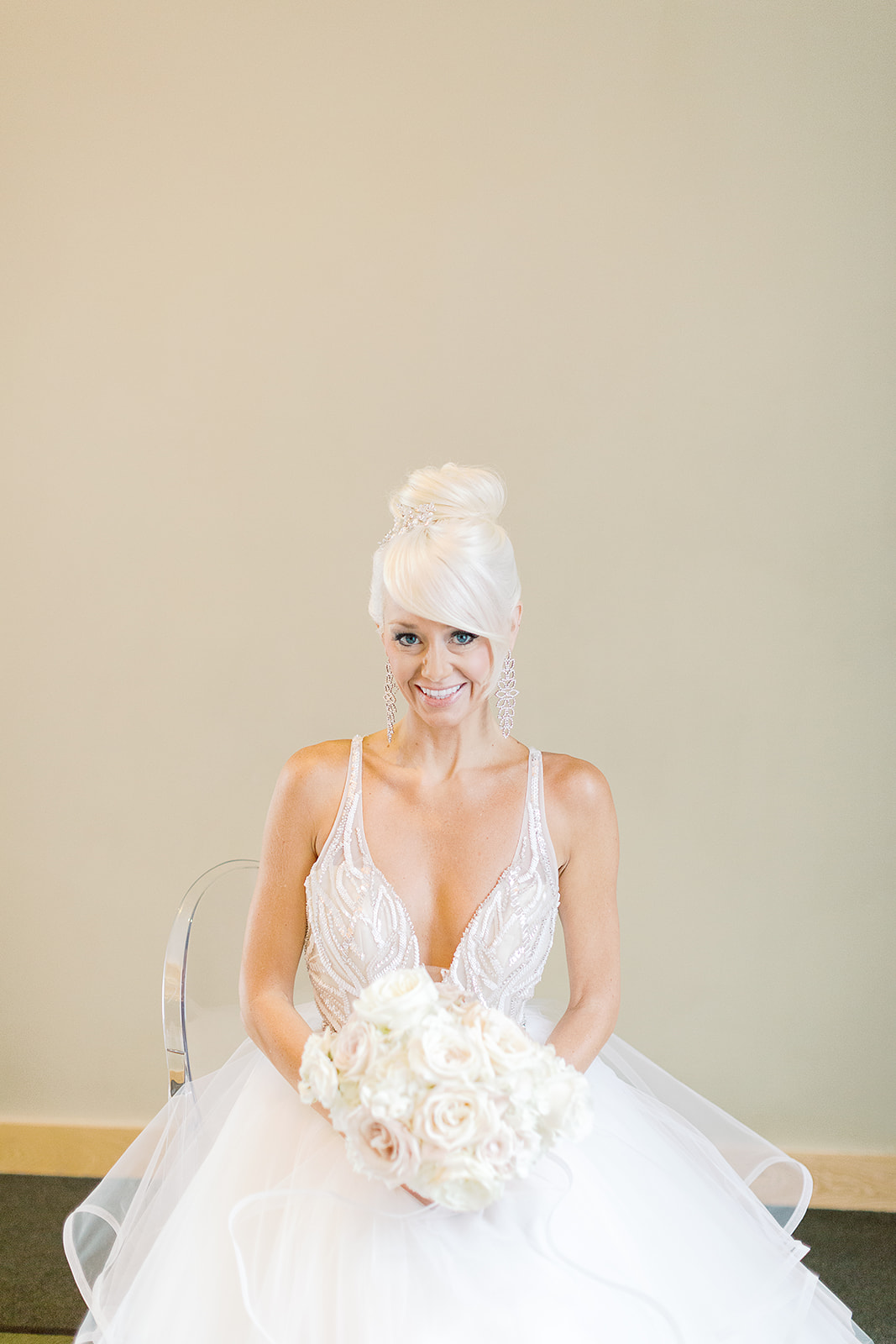 Bride in a wedding gown holding an all white rose bridal bouquet on the day of her formal white ballroom wedding in Seattle