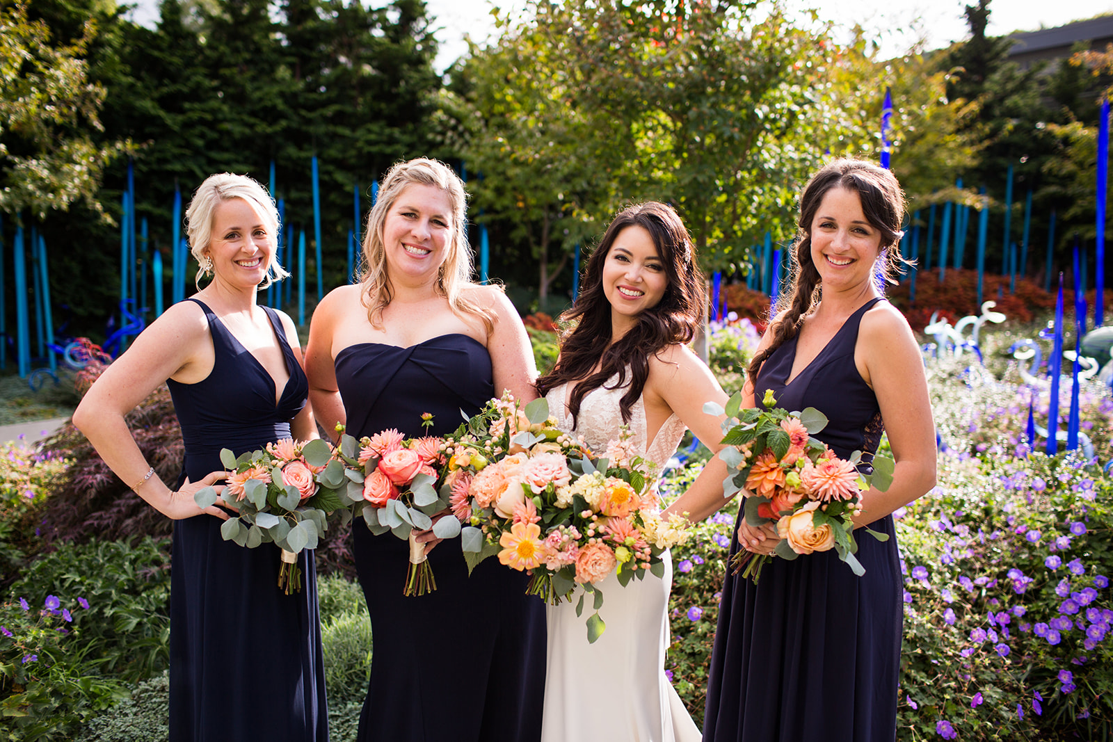 Bride and bridesmaids holding peach, coral, and orange bouquets with fall flowers | Flora Nova Design Seattle