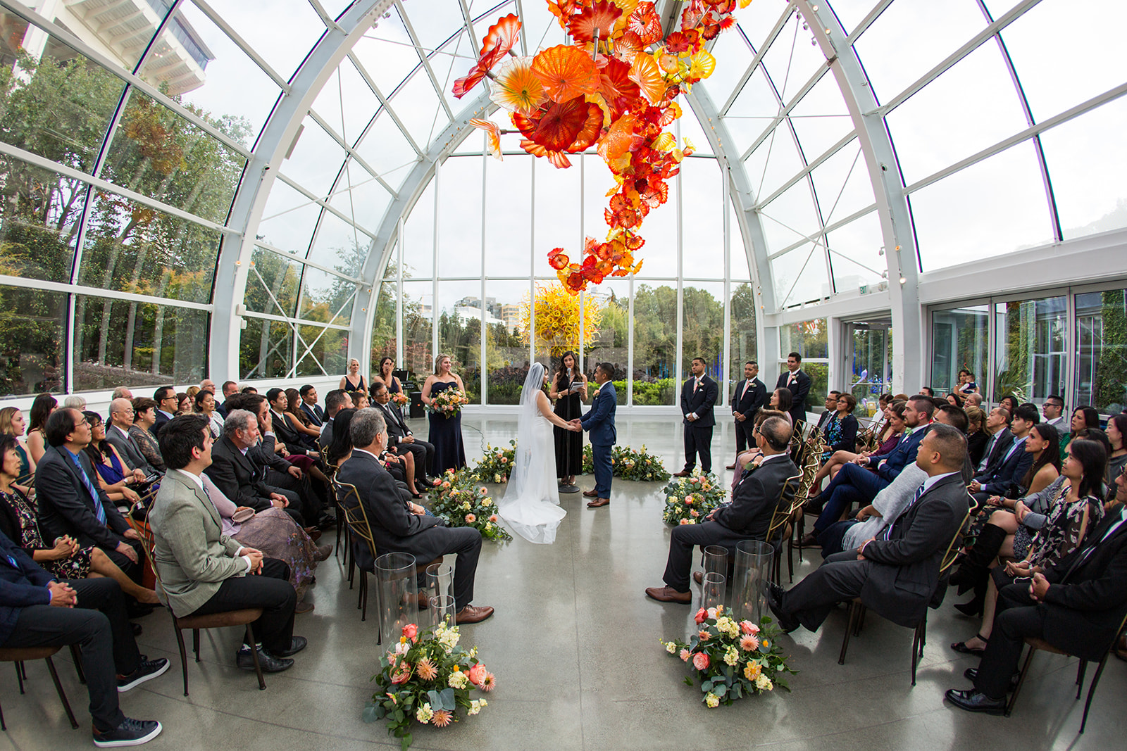 Fall navy blue and burnt orange wedding ceremony in the glass house at Chihuly, bride and groom surrounded by wedding guests | Flora Nova Design Seattle