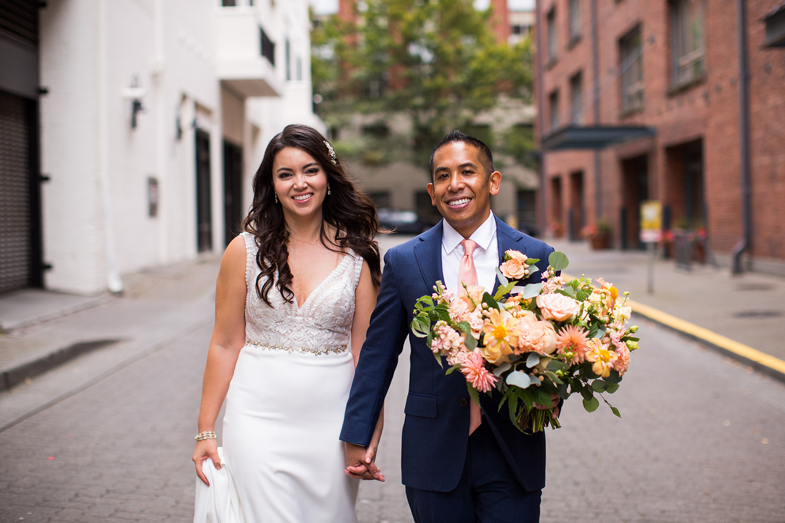 Bride and groom posing with a coral, peach and grey bridal bouquet using local dahlias for an Autumn Wedding at Chihuly Gardens and Glass | Flora Nova Design