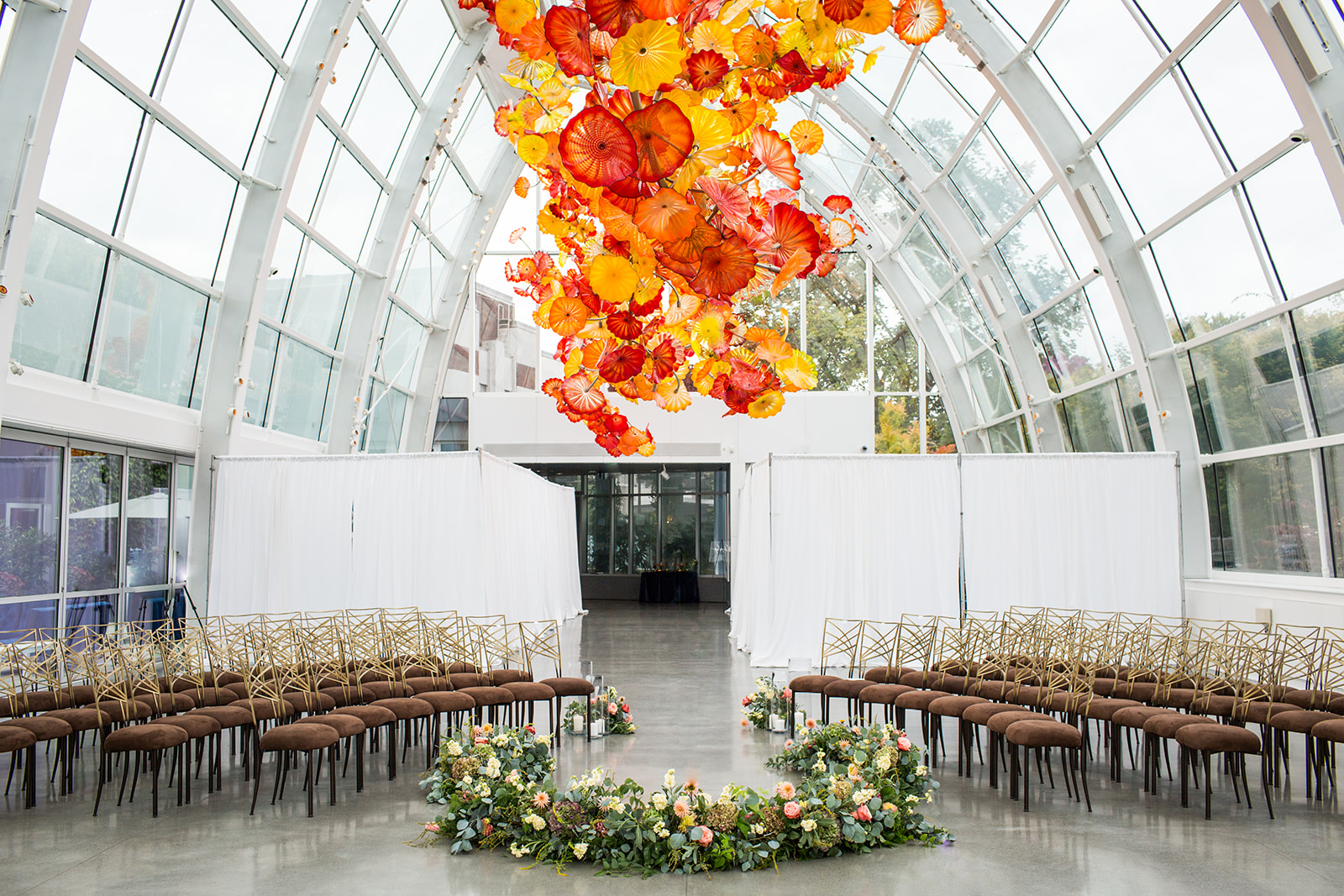 Fall ceremony navy blue and burnt orange wedding setup with low circle of flowers on the floor and guest chairs around it at Chihuly | Flora Nova Design Seattle