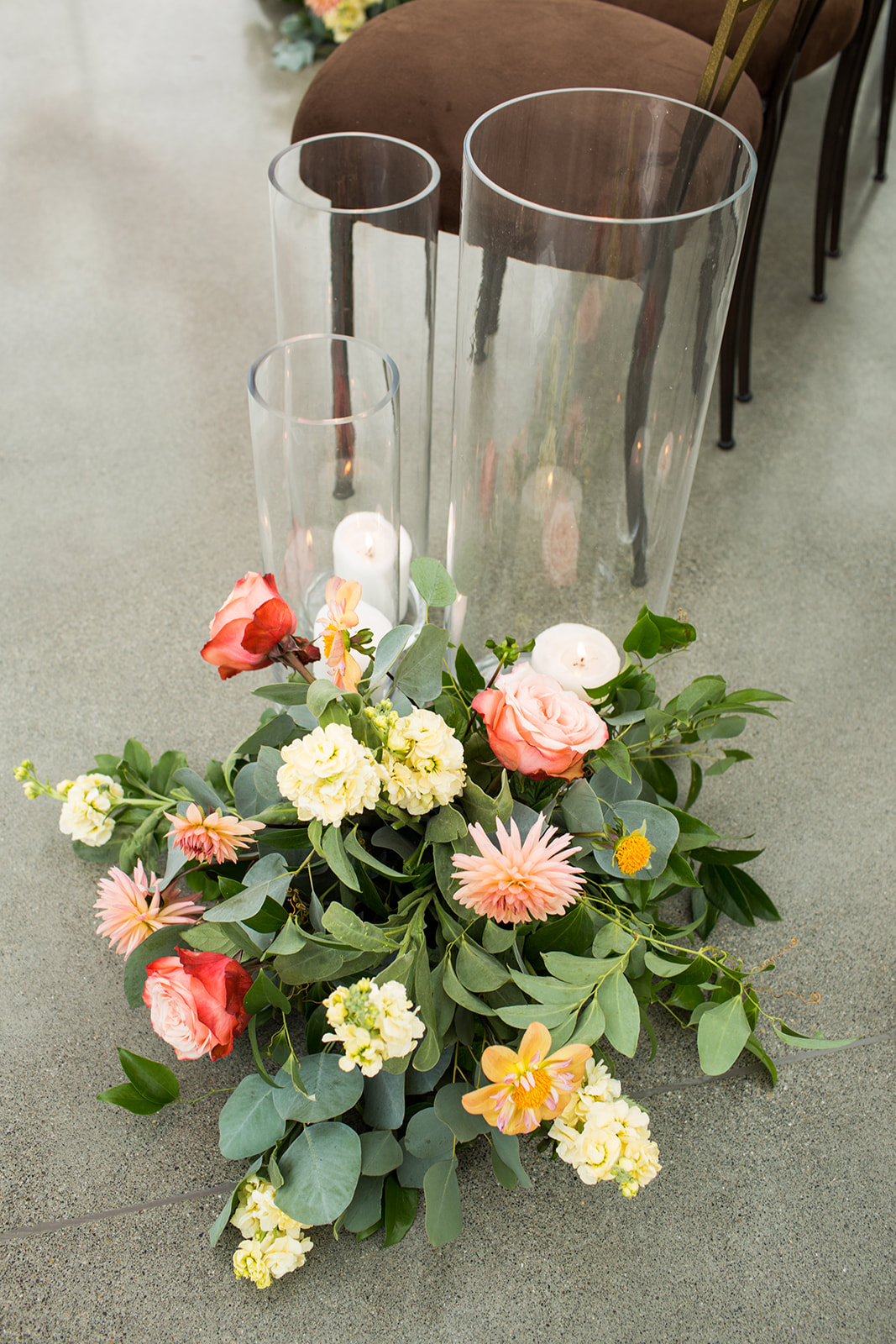 Low fall floral arrangement placed down the aisle of ceremony space with hurricane candles