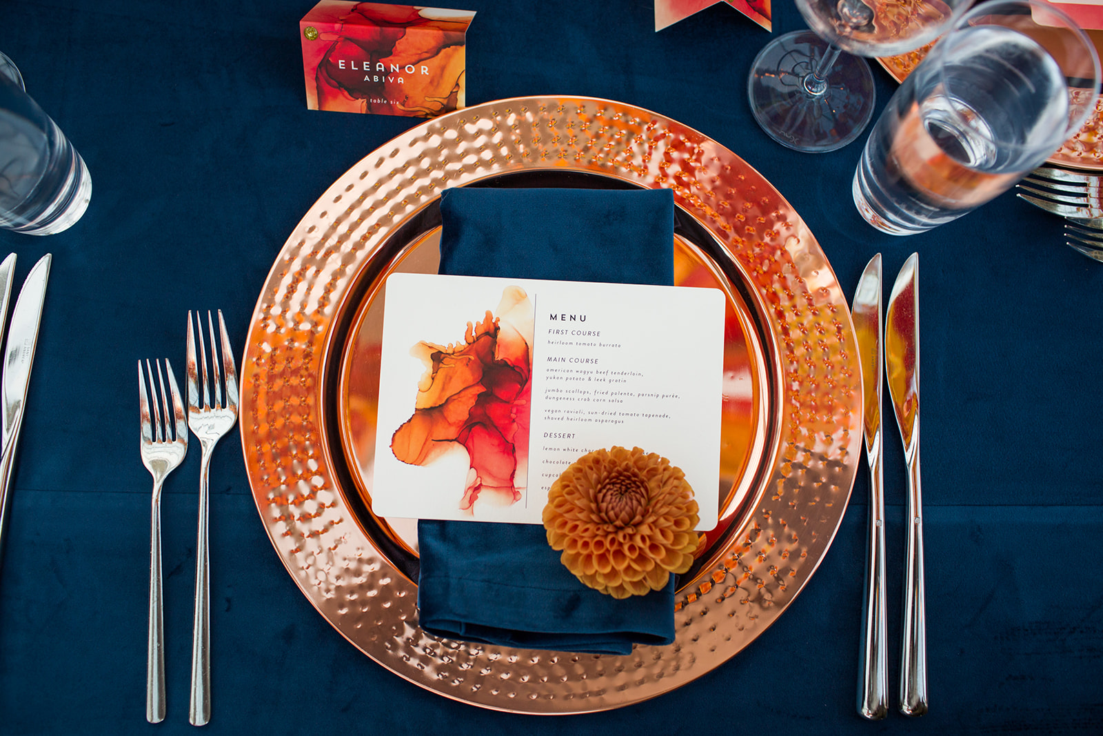 Rose gold charger plate on navy blue velvet linen with orange dahlia flower at every place setting fall wedding table setting