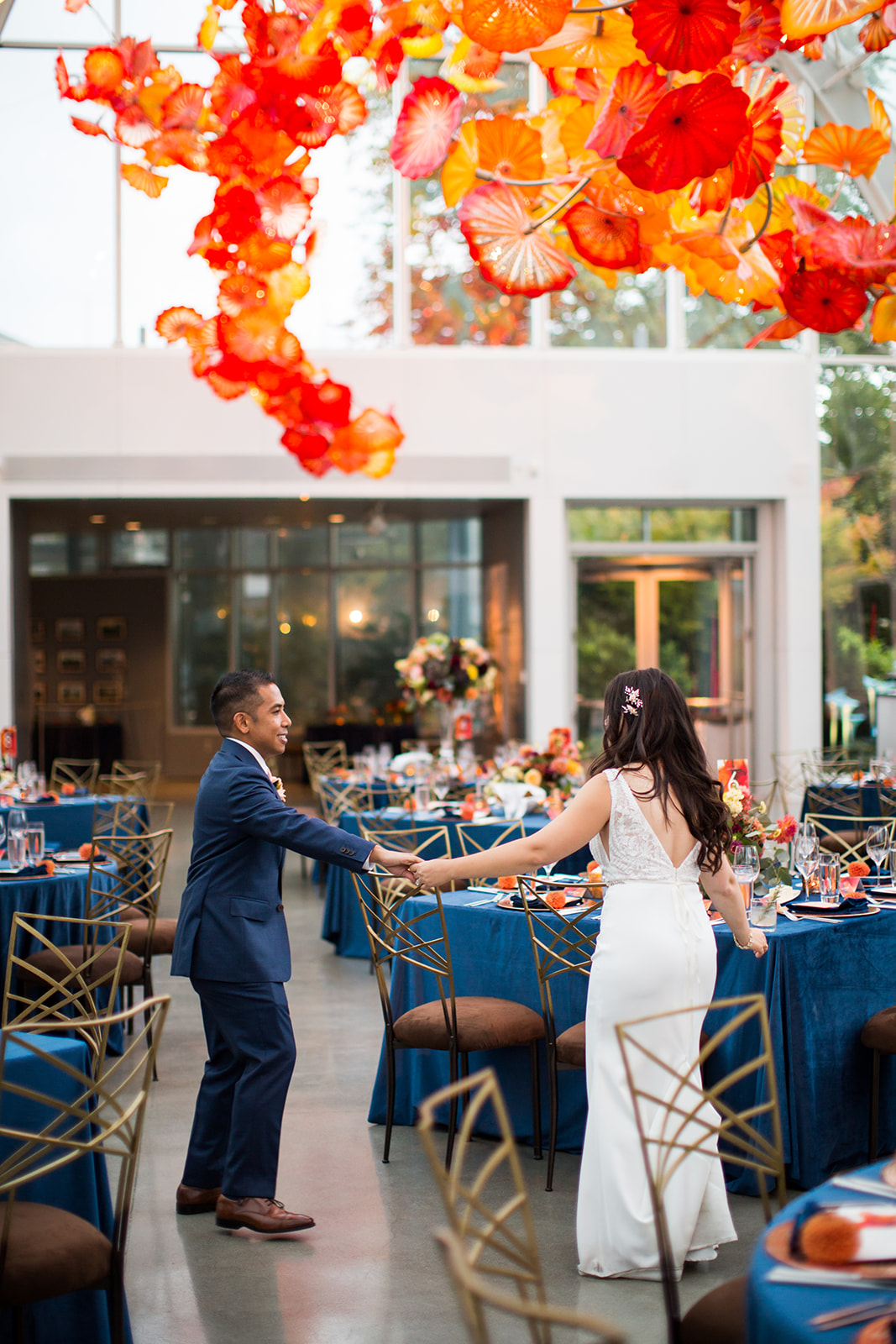 Bride and groom dancing around their reception tables at a fall Chihuly wedding | Flora Nova Design Seattle