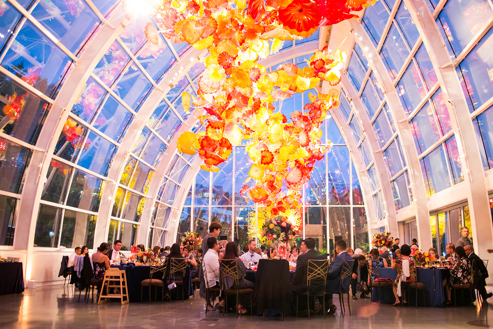 Evening at a fall wedding reception in the Chilhuly glass house